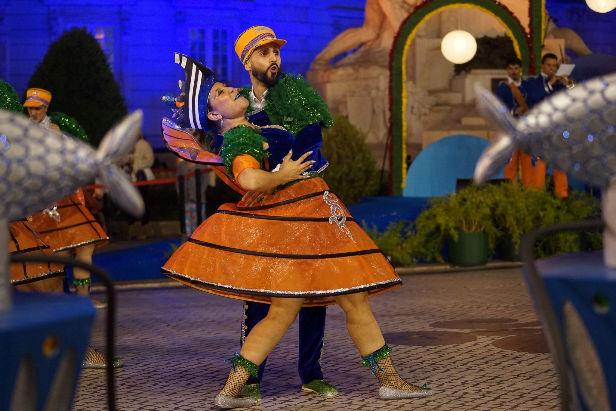 Um par de marchantes dança na Avenida da Liberdade. O homem segura a mulher nos seus braços enquanto a inclina. Ela enverga uma saia laranja e ele tem um chapéu da mesma cor.