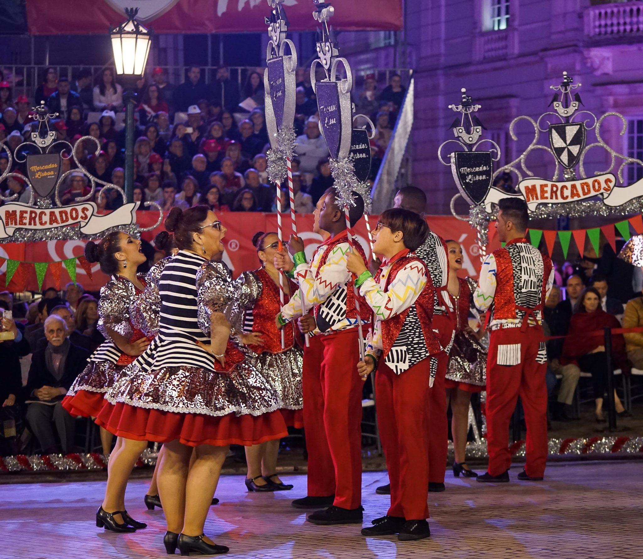 Mulheres e homens vestidos de vermelho, branco e preto, carregam os arcos e marcham na Avenida da Liberdade. Ao fundo, vêem-se bancadas com espetadores.