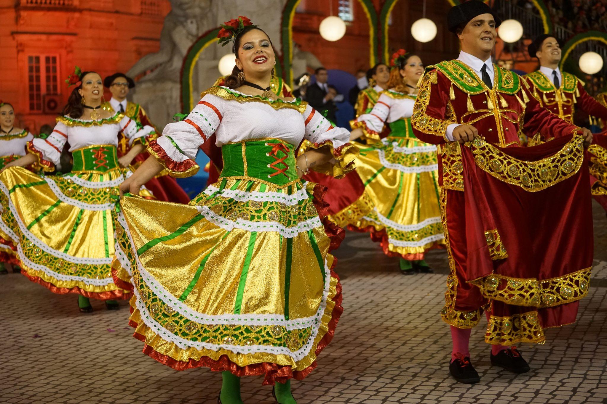 Uma mulher, com rosas na cabeça, dança com uma saia larga de cor dourada e verde. Ao seu lado, um homem vestido de toureiro em tons vermelho escuro e dourado empunha um capote. Em segundo plano, outros marchantes com a mesma roupa replicam estes gestos.