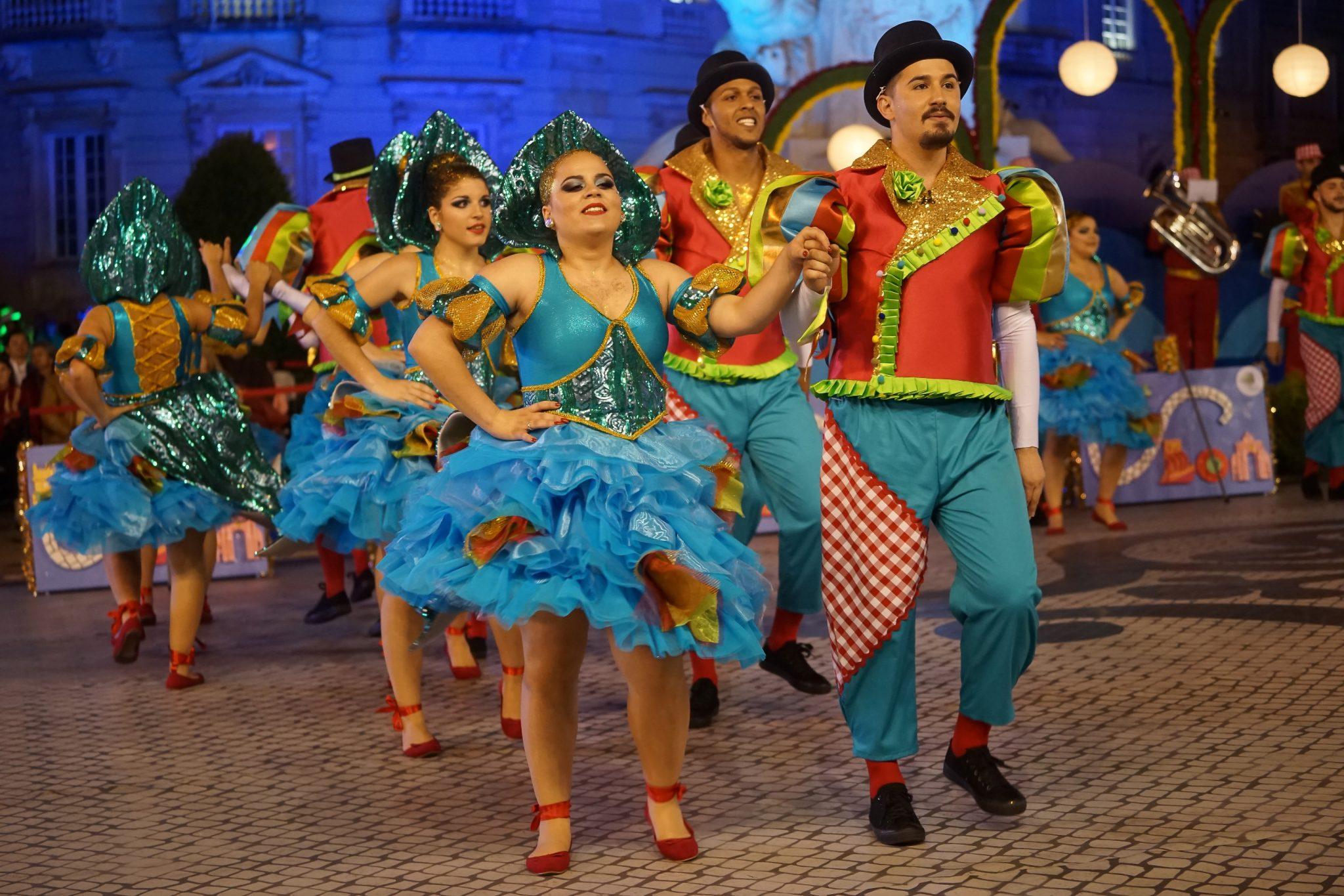 De frente para o observador, um par composto por um homem e mulher dançam lado a lado com as mãos dadas. Ela está vestida com um vestido azul e ele com um casaco vermelho e umas calças azuis. Atrás deles, em segundo plano, outros casais com a mesma roupa, marcham da mesma forma.