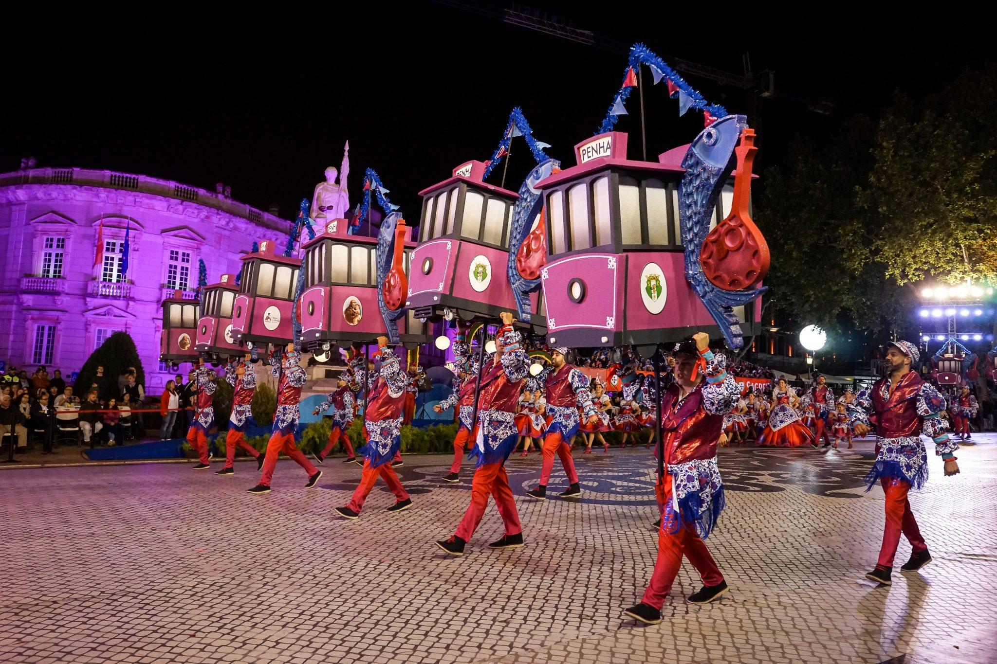 De lado para o observador, uma dezena de homens marcham para a esquerda da imagem carregando seis arcos em forma de eléctrico cor-de-rosa em cuja lateral figuram sardinhas a segurar uma guitarra portuguesa.