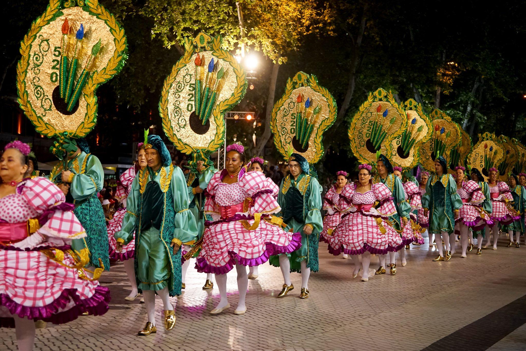 Homens e mulheres (elas com vestidos cor-de-rosa e branco e eles com trajes verdes) desfilam na Avenida da Liberdade. Trazem consigo os arcos que são paletas de pintor em tamanho gigante e de cor dourada.