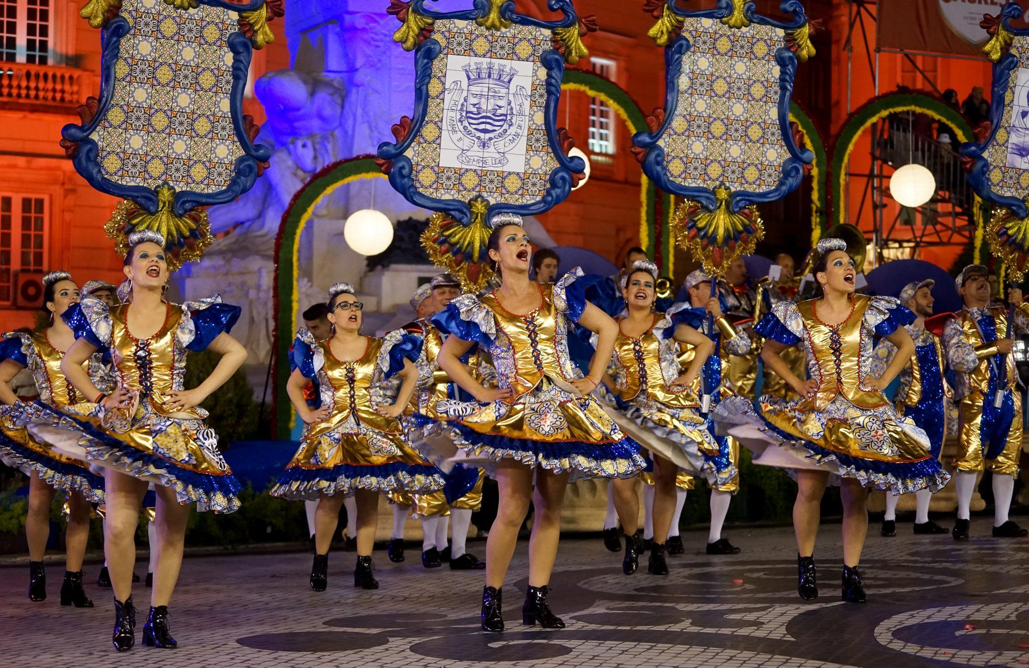 Mulheres de saia cantam e dançam na Avenida da Liberdade. Em segundo planos, os arcos da marcha que simulam azulejos.