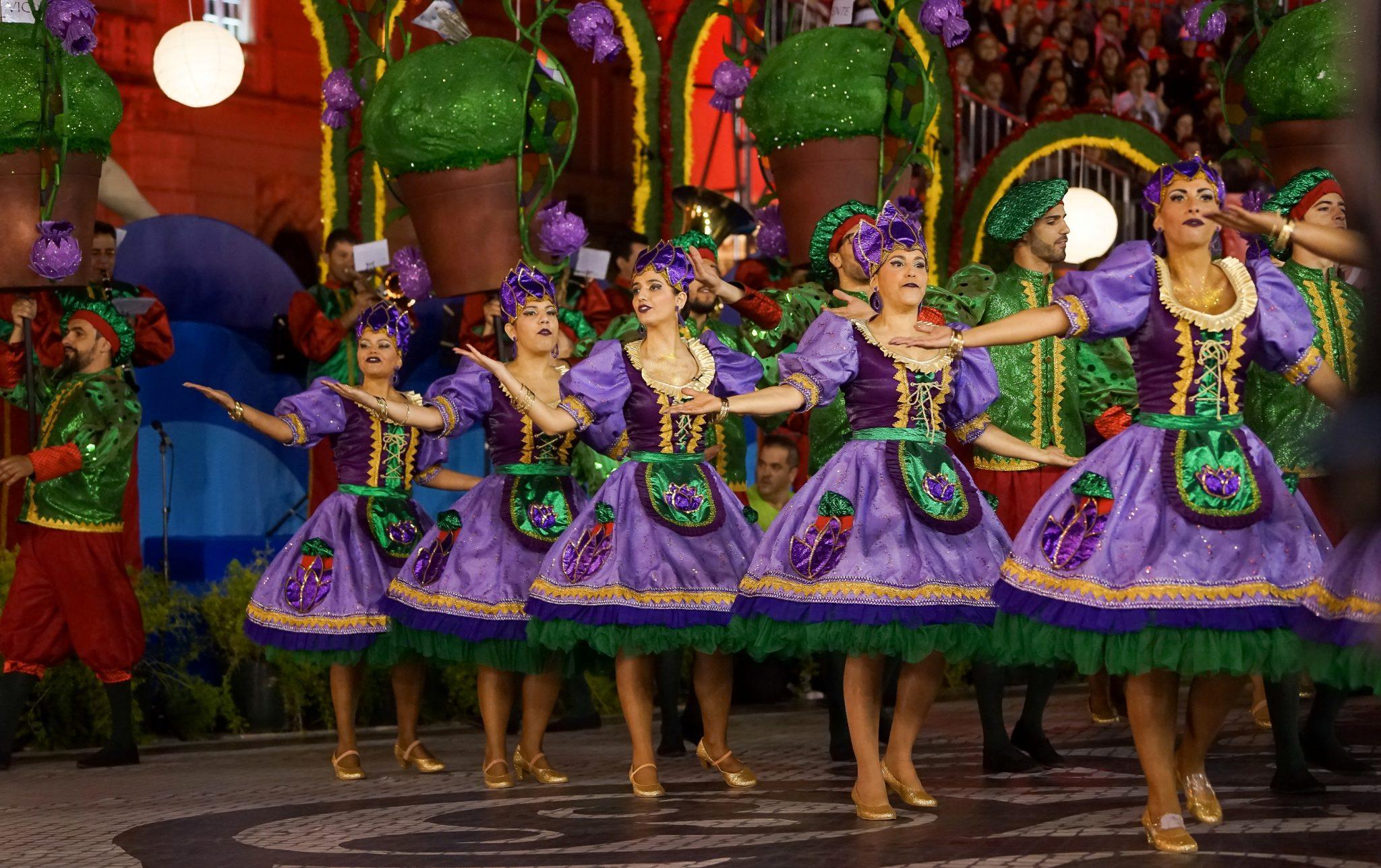 De lado para o observador, um grupo de cinco mulheres vestidas com saias rodadas roxas e um corpete da mesma cor dançam na Avenida da Liberdade. Estão de braços estendidos e em segundo planos vêem-se os arcos em forma de manjericos gigantes.