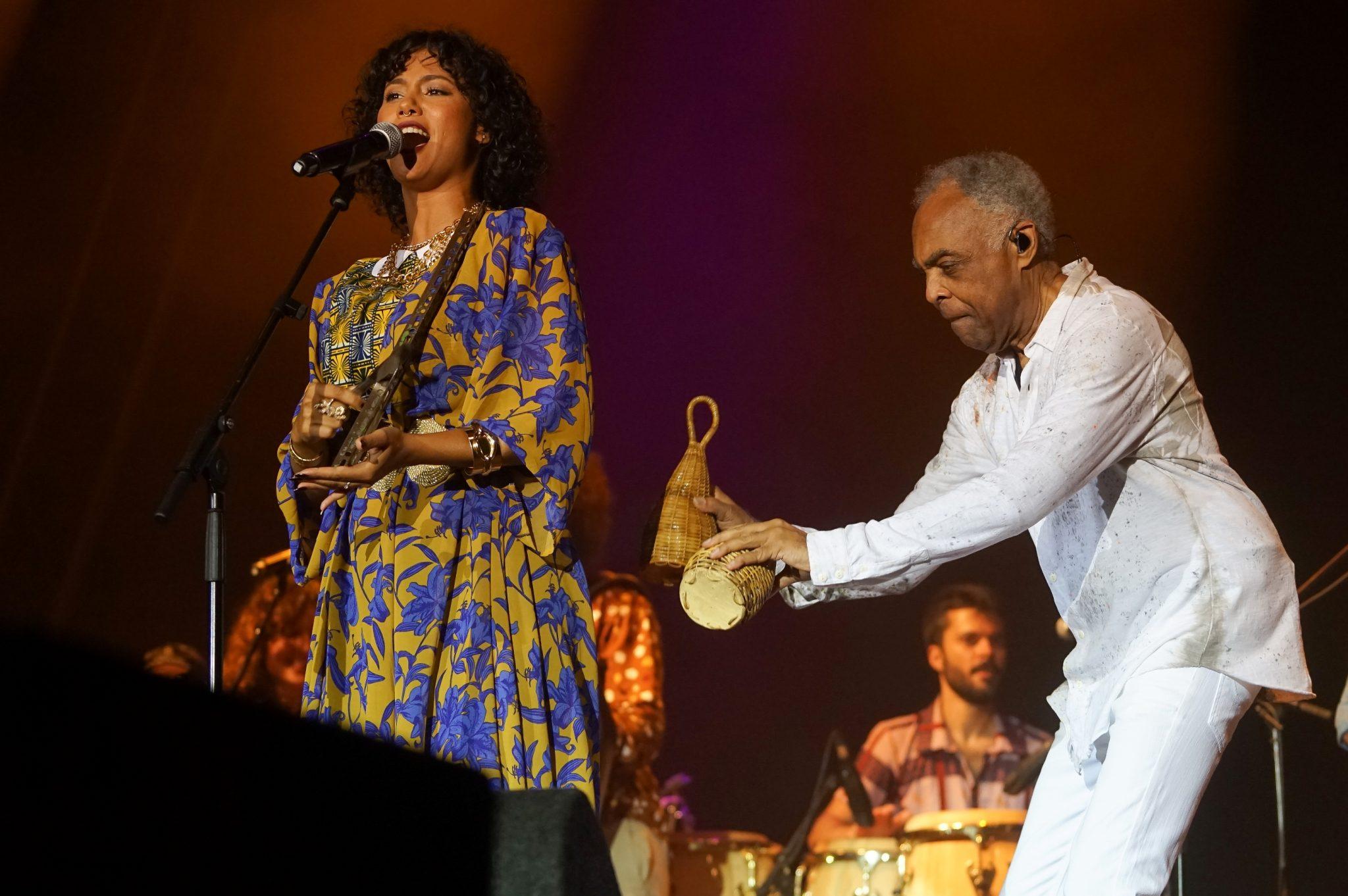 A cantora Mayra Andrade toca o instrumento cabo-verdiano ferro enquanto o músico Gilberto Gil, ao seu lado, toca o instrumento de percussão caxixi