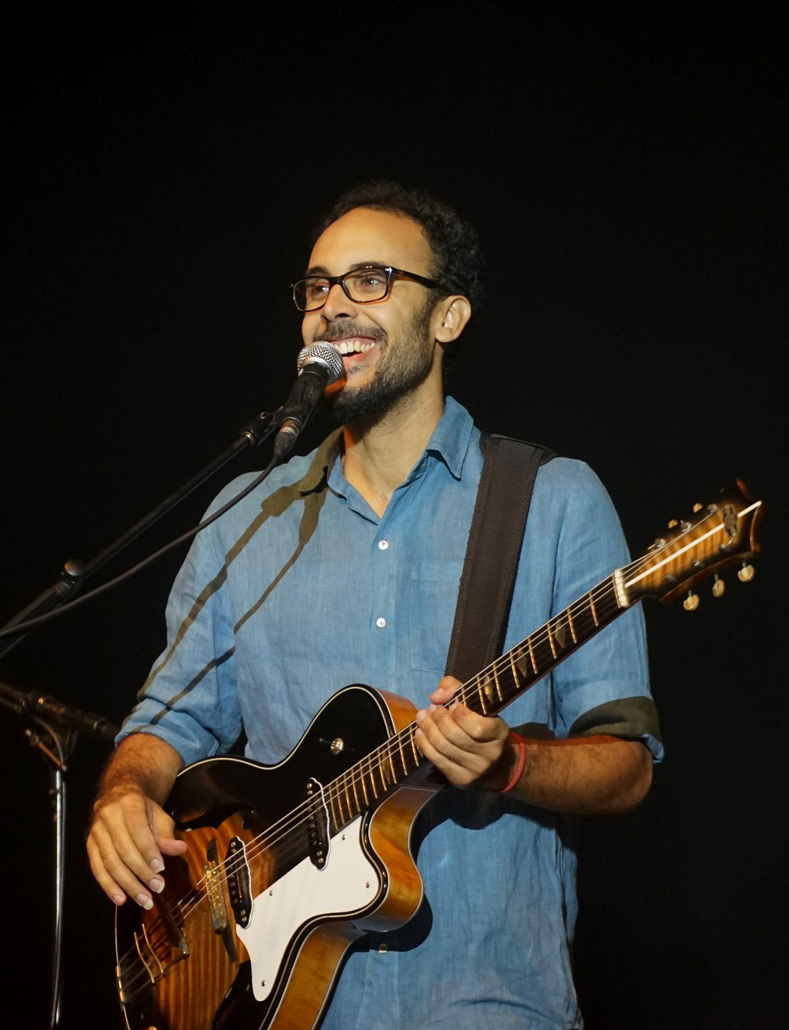 O músico brasileiro Bem Gil sorri enquanto toca guitarra durante o concerto Refavela 40