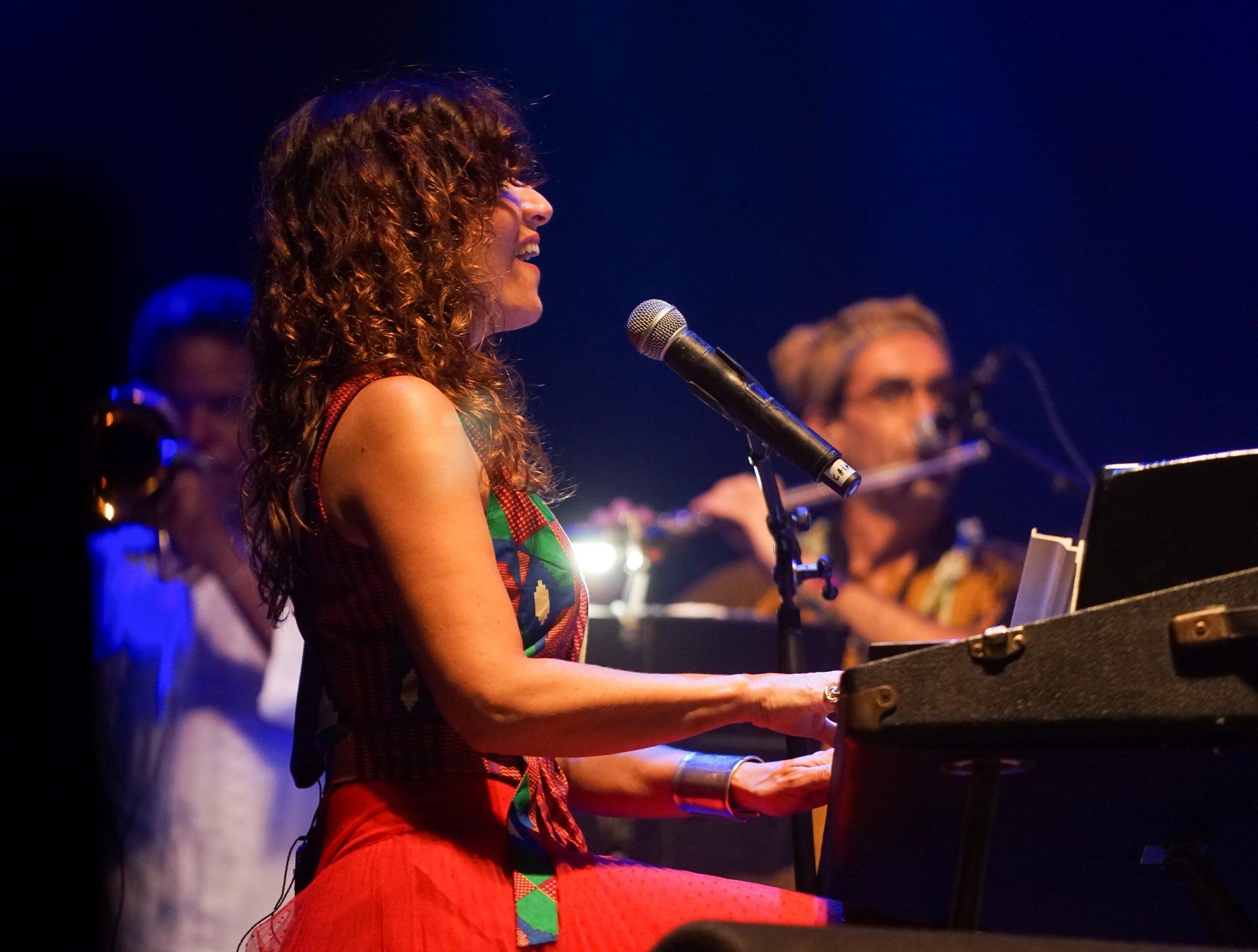 A música italiana Chiara Civello sentada ao piano durante o concerto Refavela 40