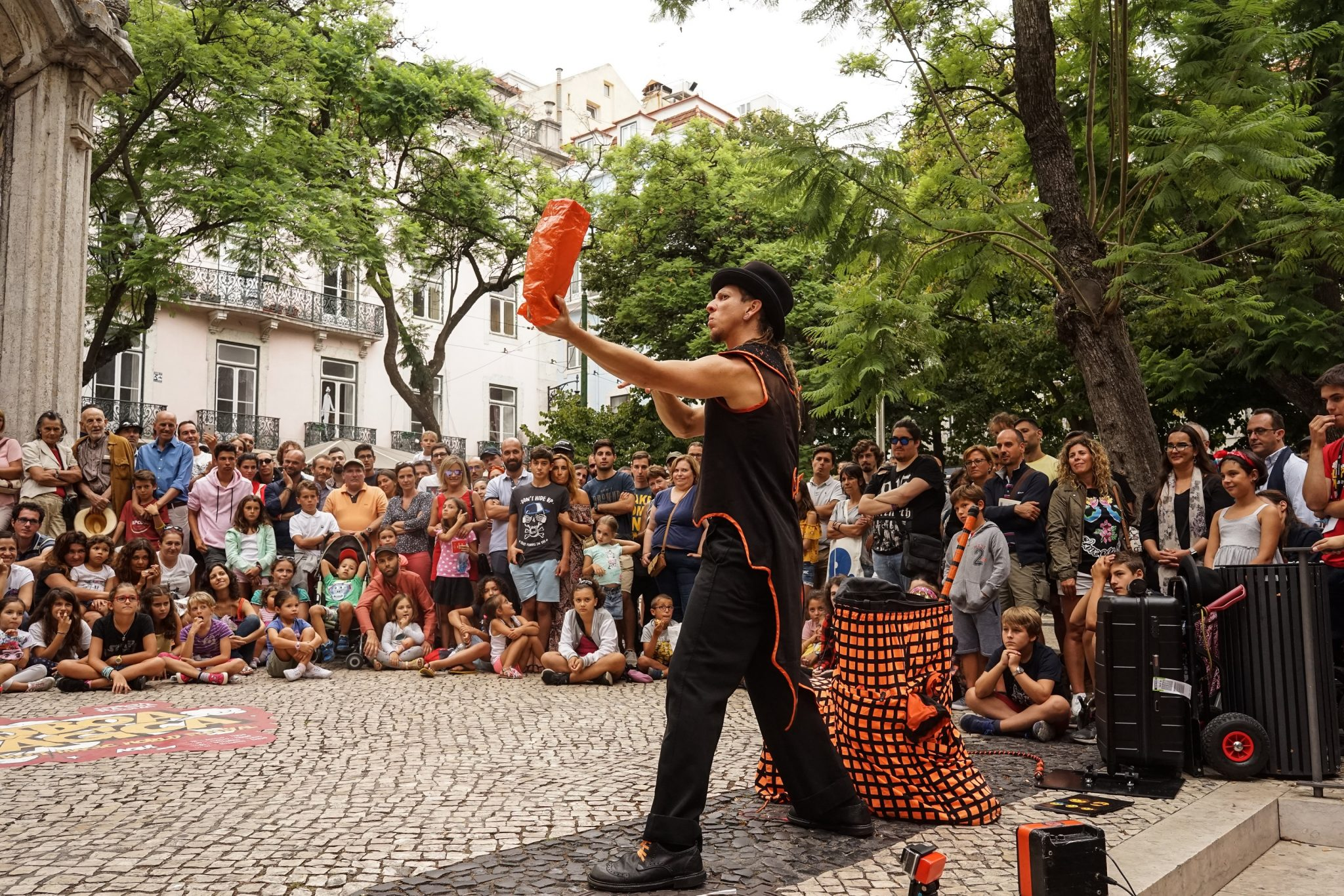 De lado para o observador, no centro da imagem, um homem com roupa preta e laranja e um chapéu preto, segura na palma da mão um pequeno saco cor de laranja. À sua volta, crianças e adultos, sentados e de pé, de frente para o observador, assistem ao espetáculo.