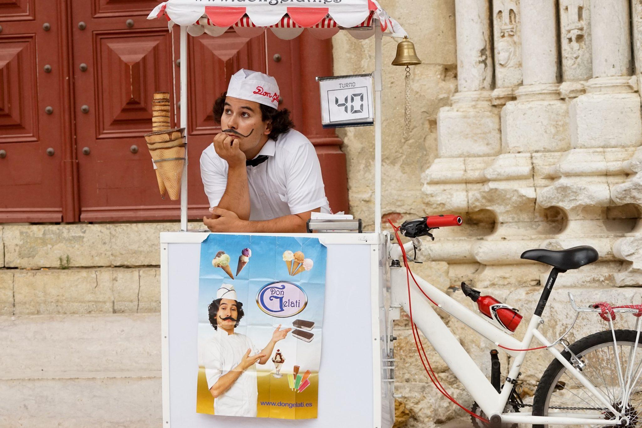 Um homem de bigode, chapéu branco e roupa branca, com laço preto, está inclinado e apoiado numa banca de gelados
