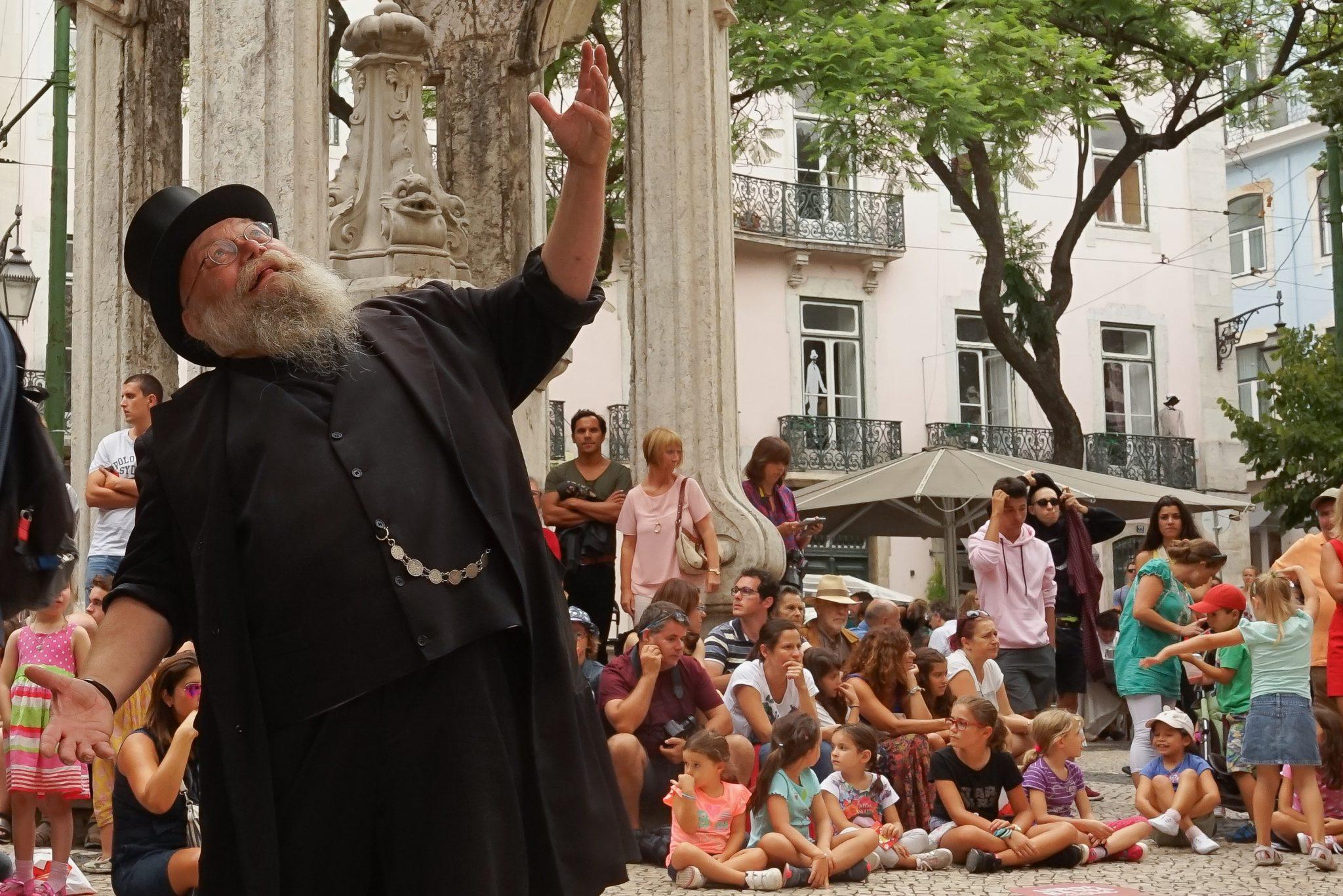 Um homem vestido de preto, com grandes barbas e um chapéu preto, está de frente para o observador, com o braço levantado e a olhar para o céu. Atrás de si, pessoas sentadas e de pé observam