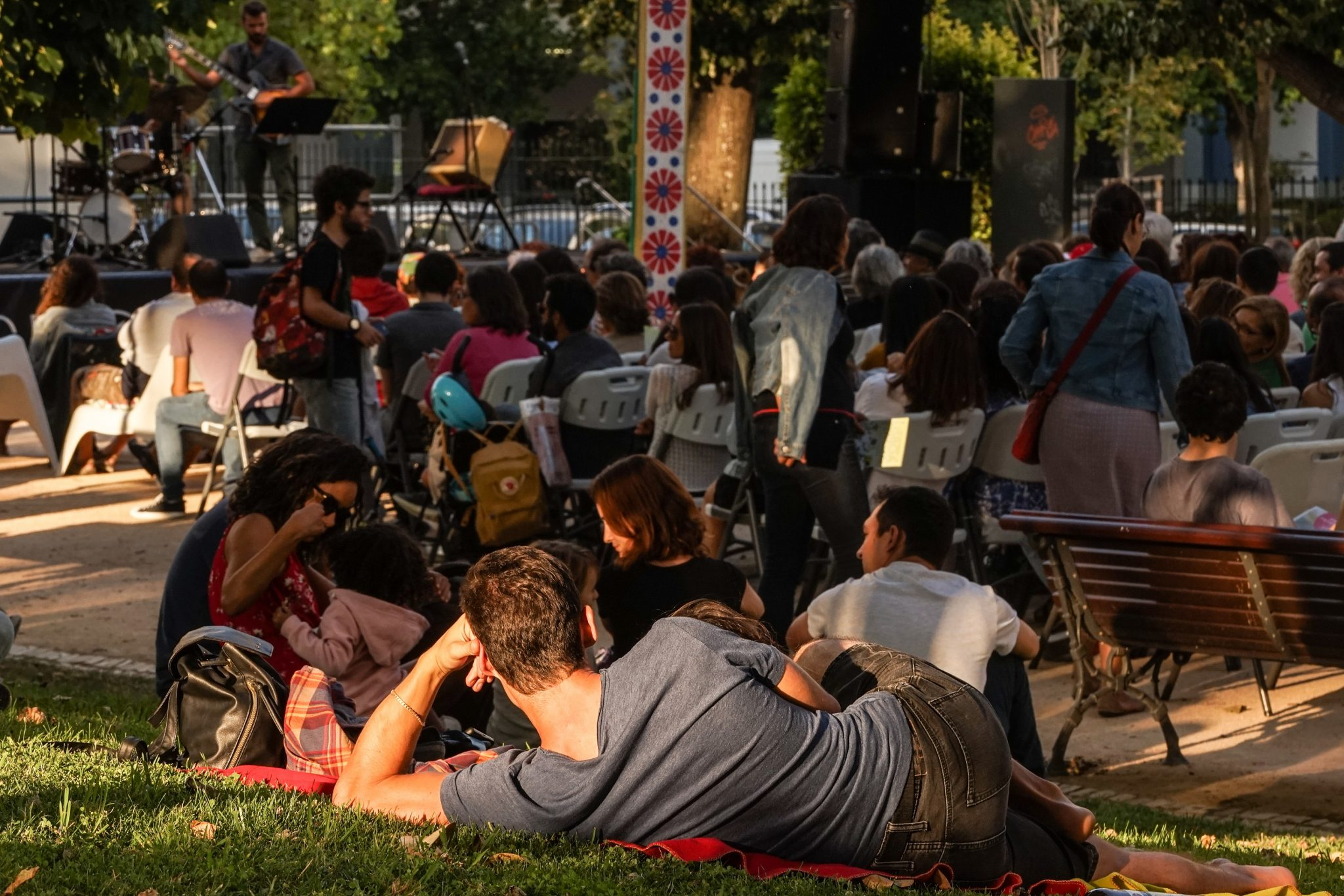 Pessoas sentadas em cadeiras e deitadas na relva a assistir a um concerto