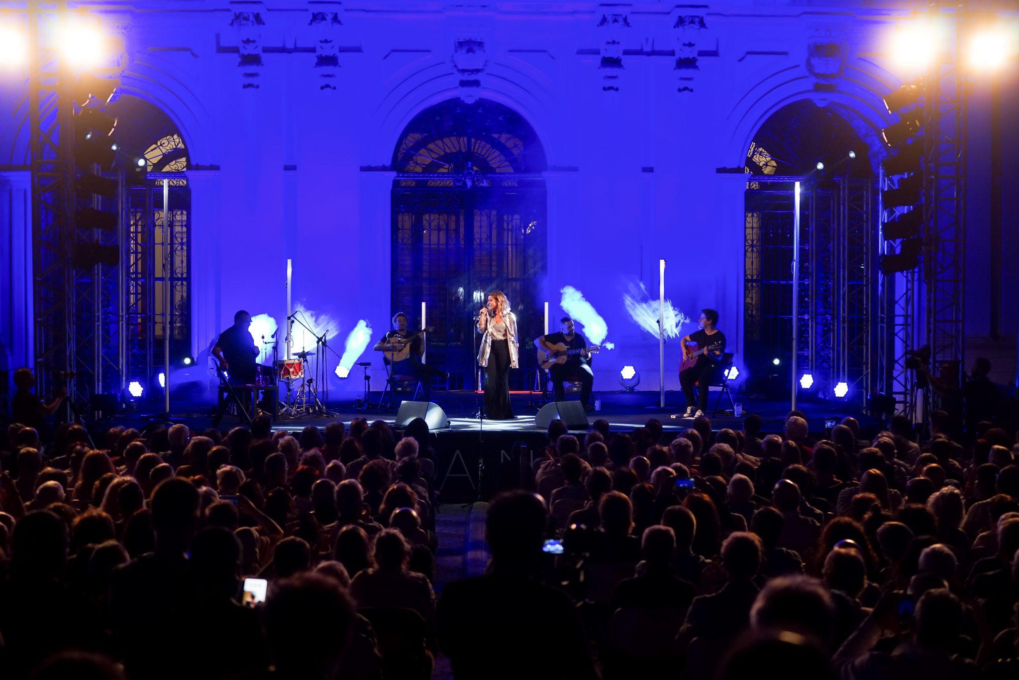 Num primeiro plano, de costas para o observador, a silhueta de várias pessoas sentadas. Ao fundo, sob iluminação azul, o palco e os músicos