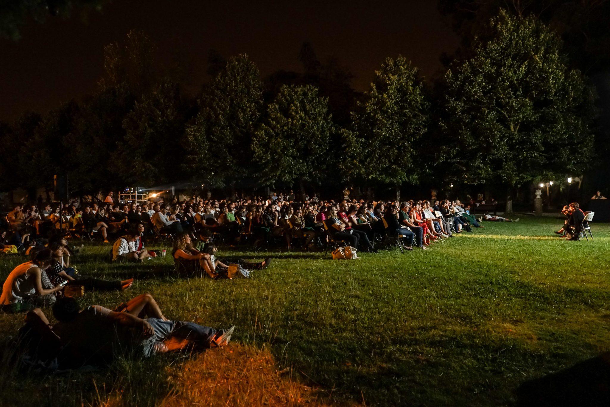 Jardim, à noite, com várias pessoas sentadas em cadeiras e no chão, iluminadas por um écrã de cinema.