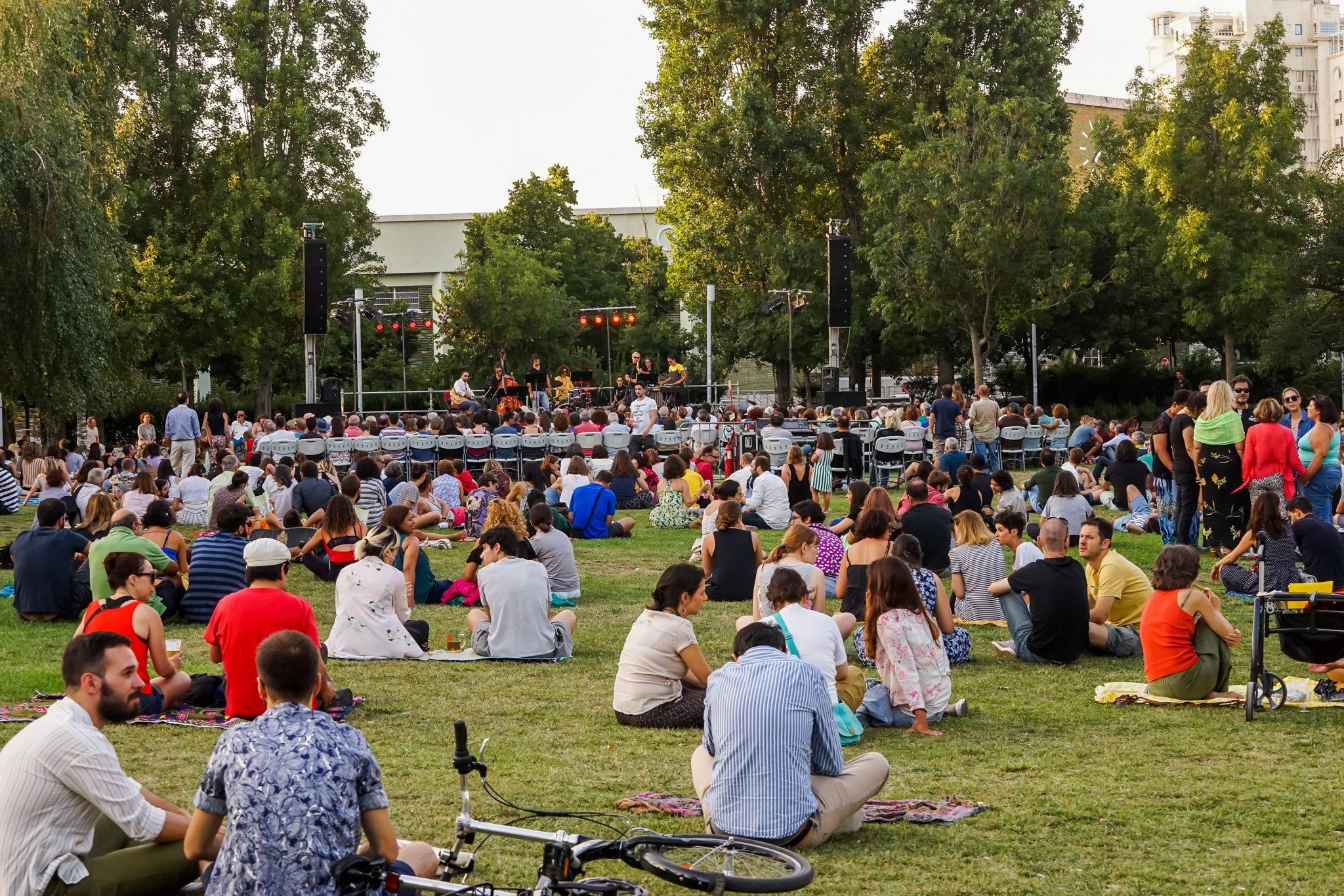 Pessoas sentadas num jardim a assistir a um concerto durante o dia