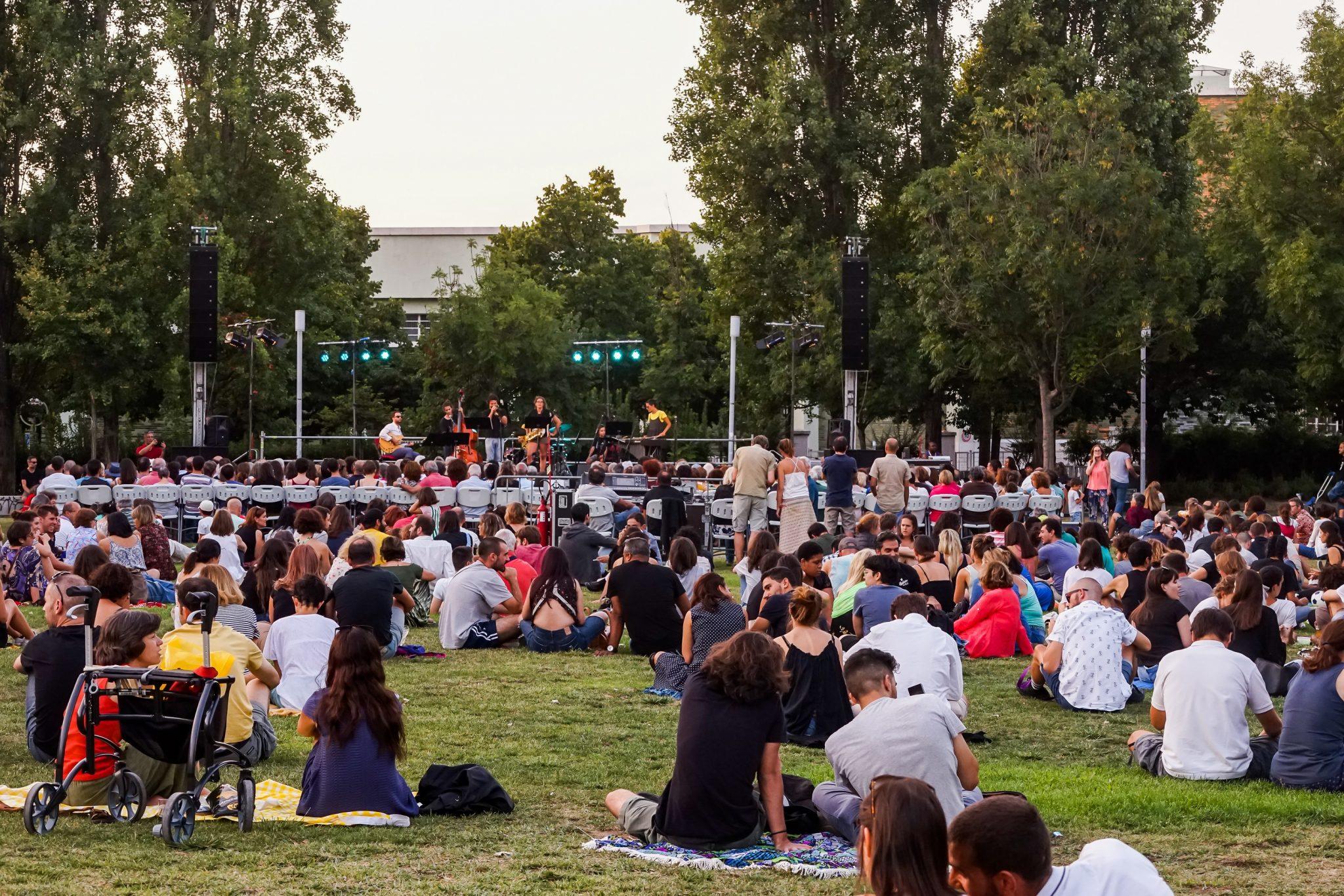 Pessoas sentadas no chão, num jardim, de costas para o observador, de frente para o um palco onde estão vários músicos