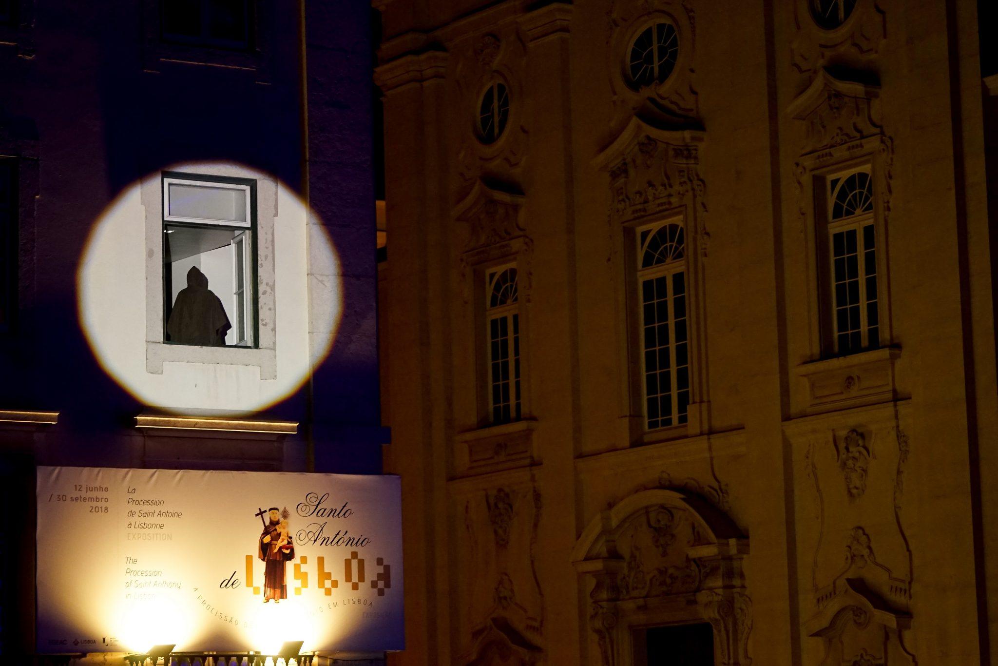 Um foco ilumina uma janela num edifício da Praça do Município, onde se vê uma figura com um capa e capuz