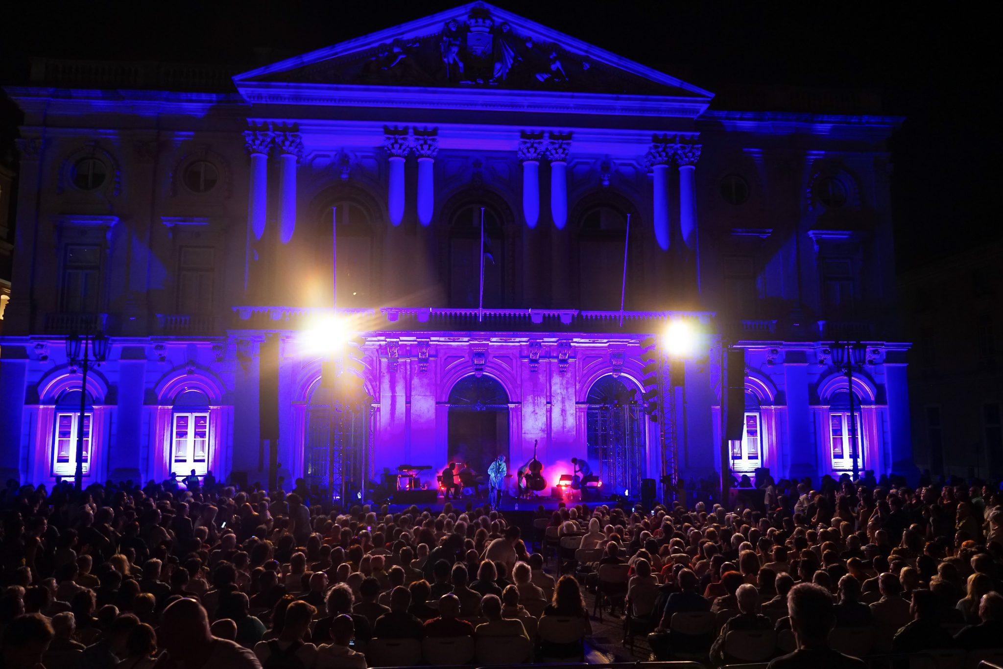 De costas para o observador, a silhueta de várias pessoas sentadas a assistir ao concerto de Paulo Bragança. Ao fundo o edifício dos Paços do Concelho com dois grandes focos e iluminado em tons de azul.