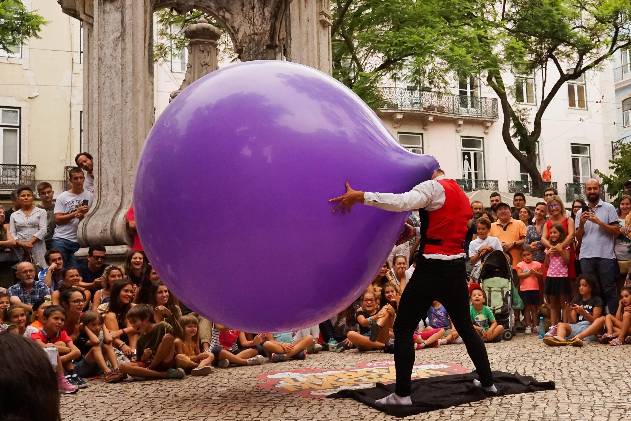 Um homem de pé, no centro de uma roda formada por pessoas sentadas, está com a cabeça dentro de um gigante balão de plástico.