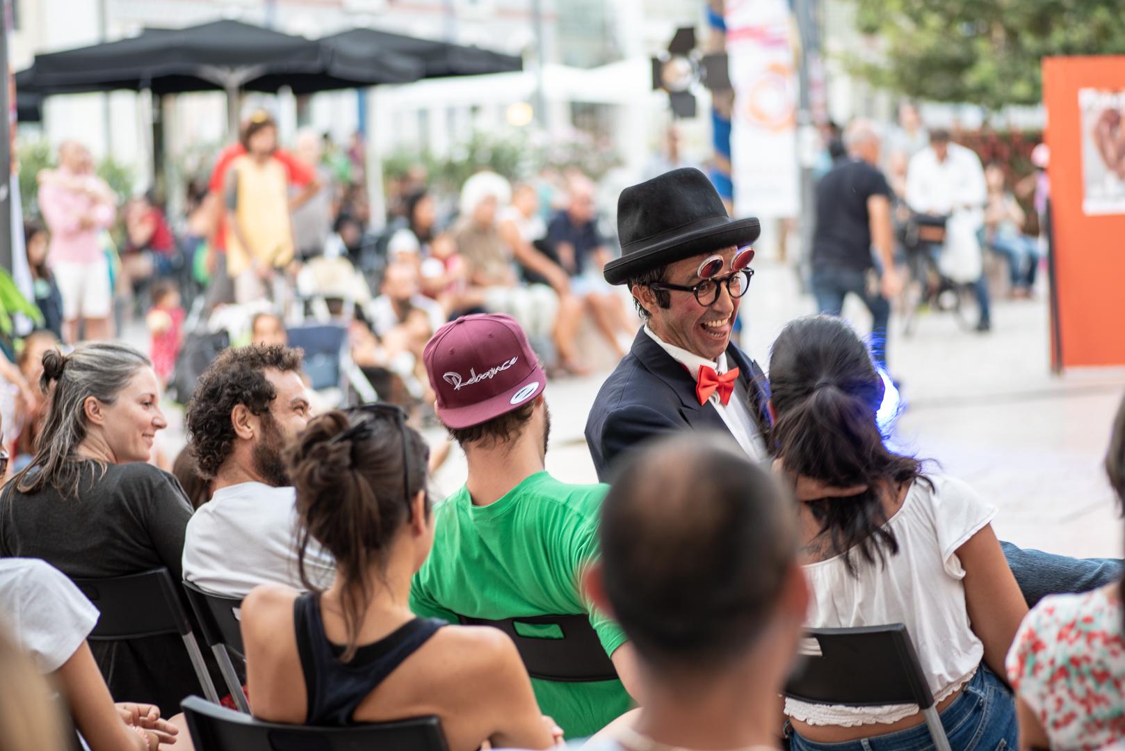 Pessoas sentadas em cadeiras de costas para o observador que interagem com um homem que sorri, com a língua de fora, de lado para o observador, com um chapéu preto, óculos e um laço vermelho