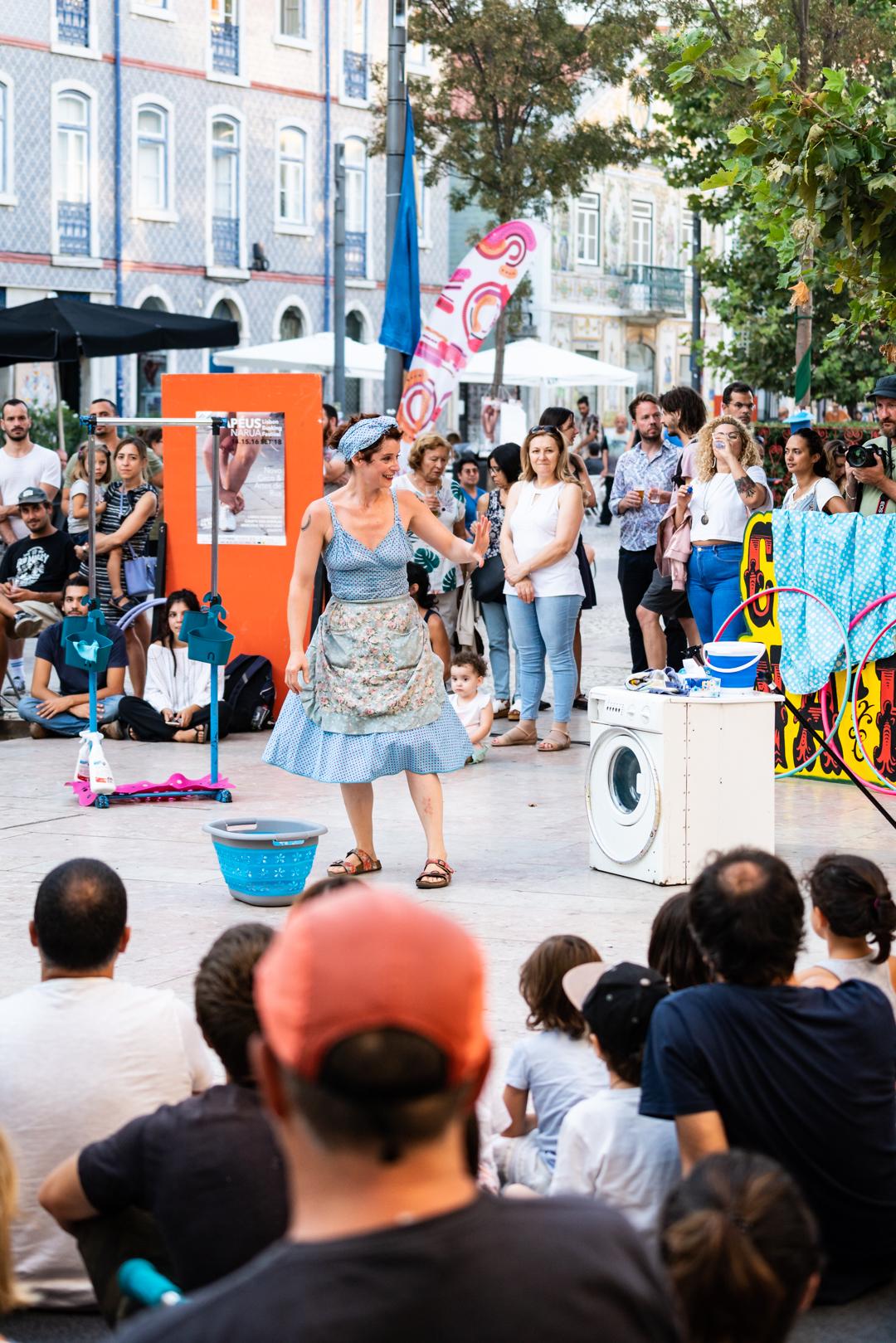 Pessoas de frente e de costas para o observador, sentadas em círculo no meio de uma praça. No meio desse círculo estão uma mulher, de pé, de frente para o observador, uma máquina de lavar roupa e um cesto.