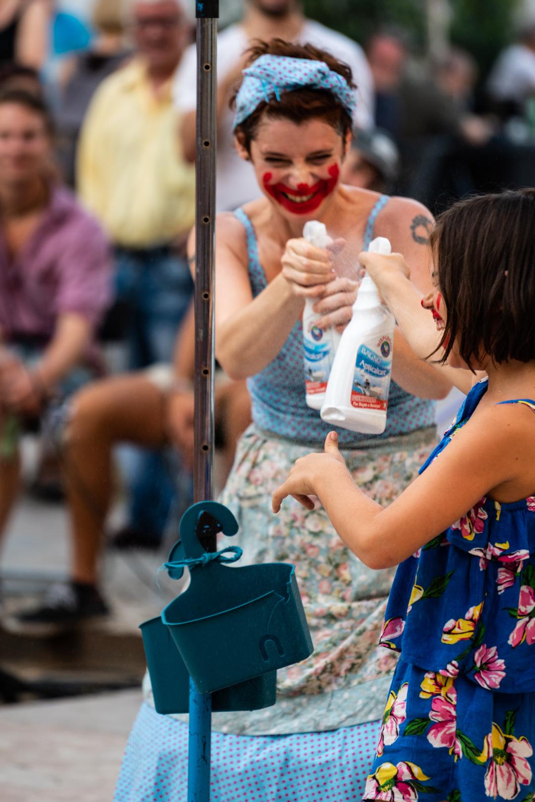Mulher, de frente para o observador, com vestido e lenço azuis e com uma pintura vermelha na cara, a brincar com criança também de vestido azul, de lado para o observador, e com a mesma pintura vermelha na cara. Cada uma segura uma garrafa aspersor, numa batalha de água.