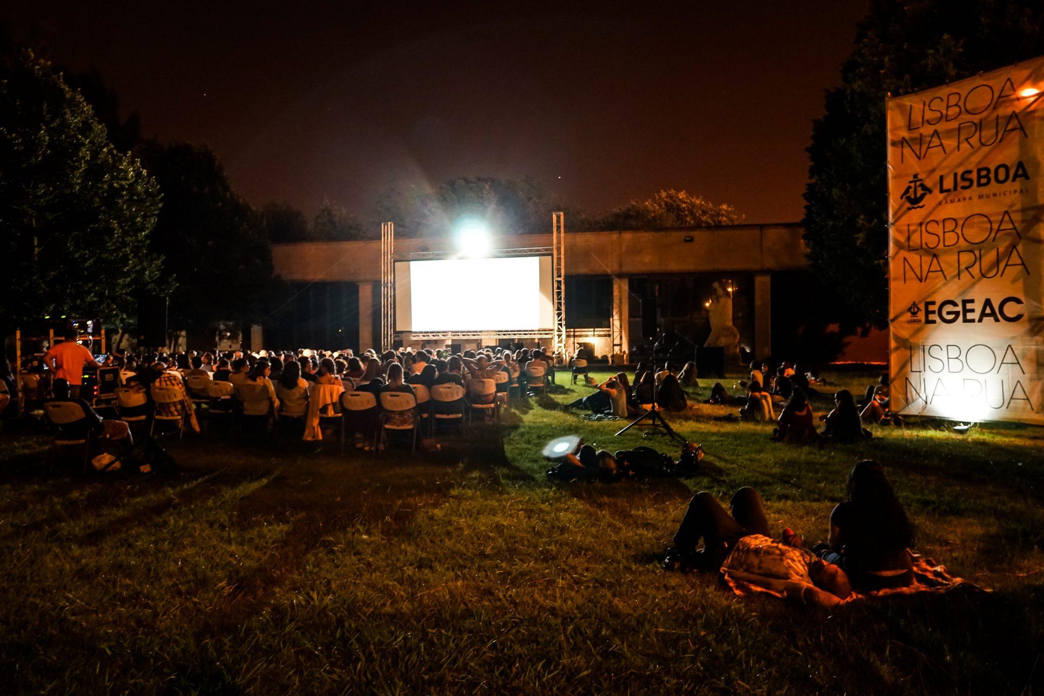Pessoas sentadas em cadeiras e no chão, na relva, de costas para o observador, virados para uma tela de cinema no jardim do Palácio Pimenta.