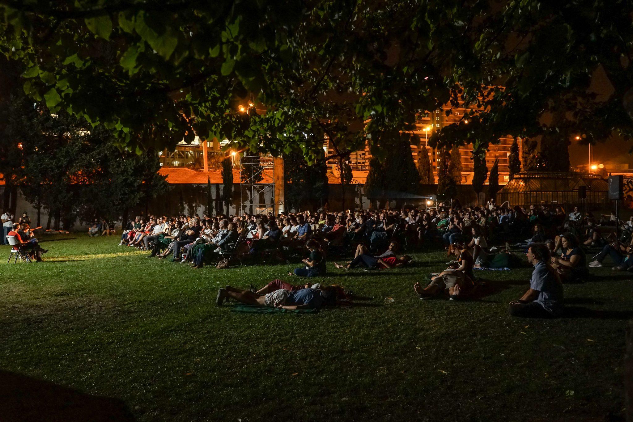 Pessoas sentadas em cadeiras e no chão, na relva, de lado para o observador, virados para uma tela de cinema no jardim do Palácio Pimenta.