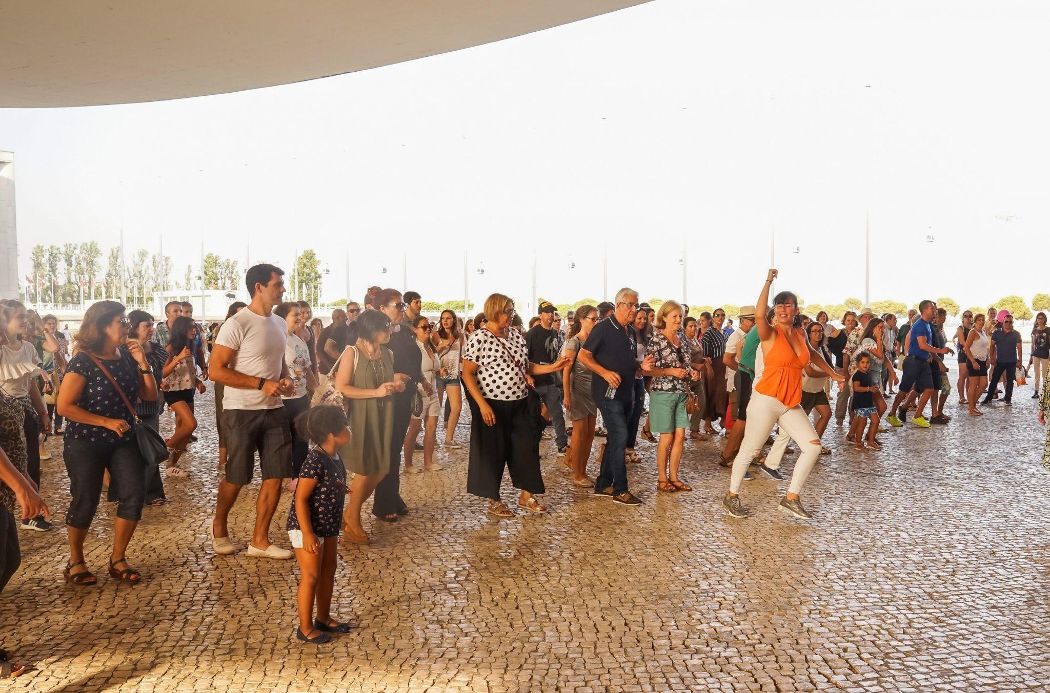 Pessoas a dançar, seguindo os passos de uma mulher, debaixo da pala do Pavilhão de Portugal no Parque das Nações