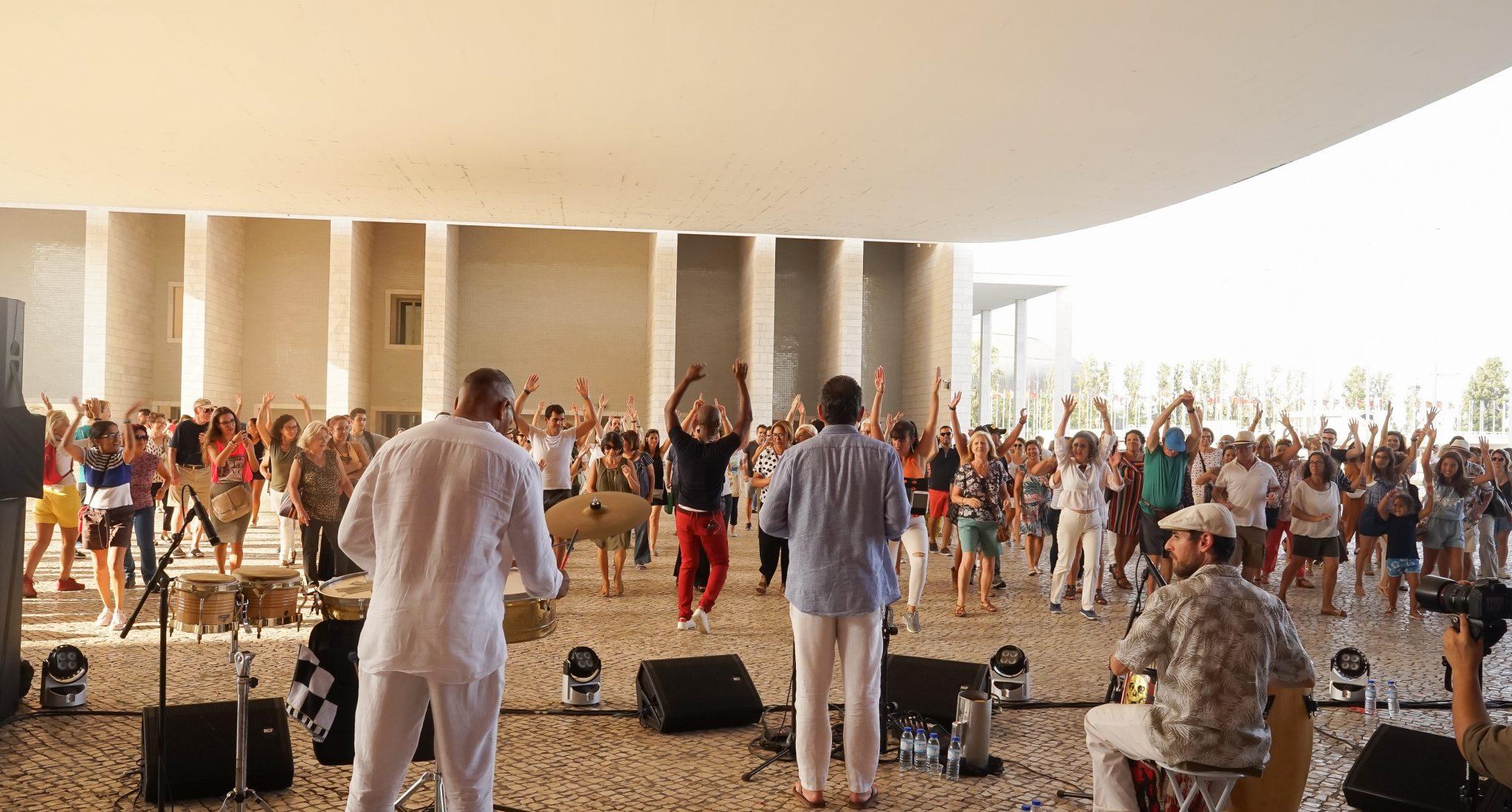 Pessoas a dançar, seguindo os passos de um homem, ao som dos ritmos tocados pelos músicos em primeiro plano, debaixo da pala do Pavilhão de Portugal no Parque das Nações