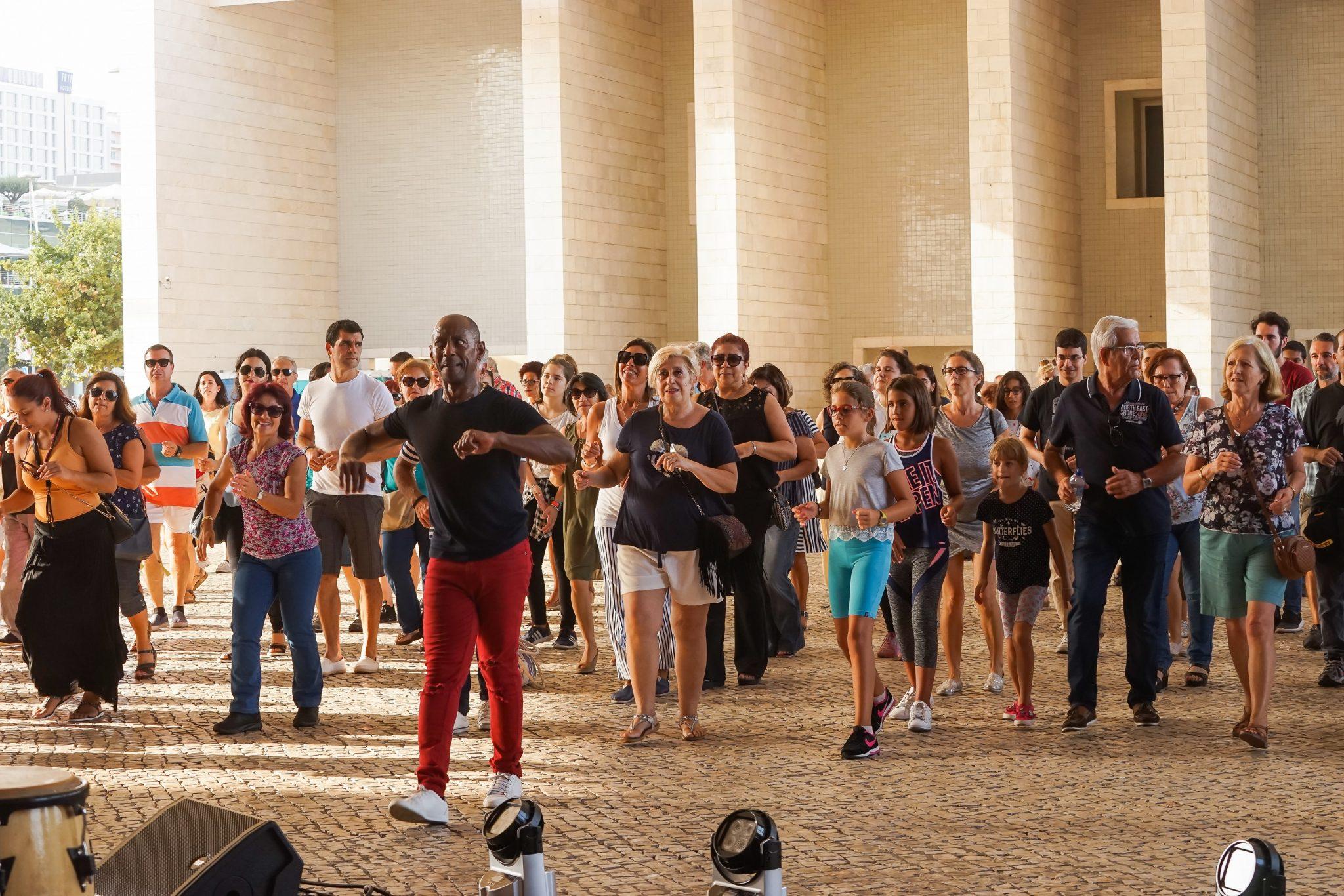 Pessoas a dançar, seguindo os passos de um homem que está em primeiro plano na imagem, todos de frente para o observador, debaixo da pala do Pavilhão de Portugal no Parque das Nações