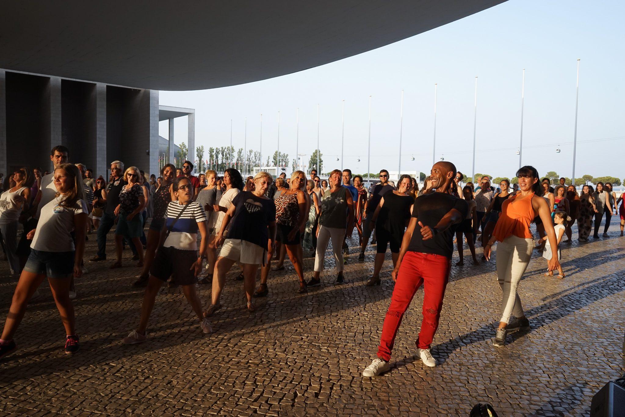 Pessoas a dançar, seguindo os passos de um homem e de uma mulher, debaixo da pala do Pavilhão de Portugal no Parque das Nações