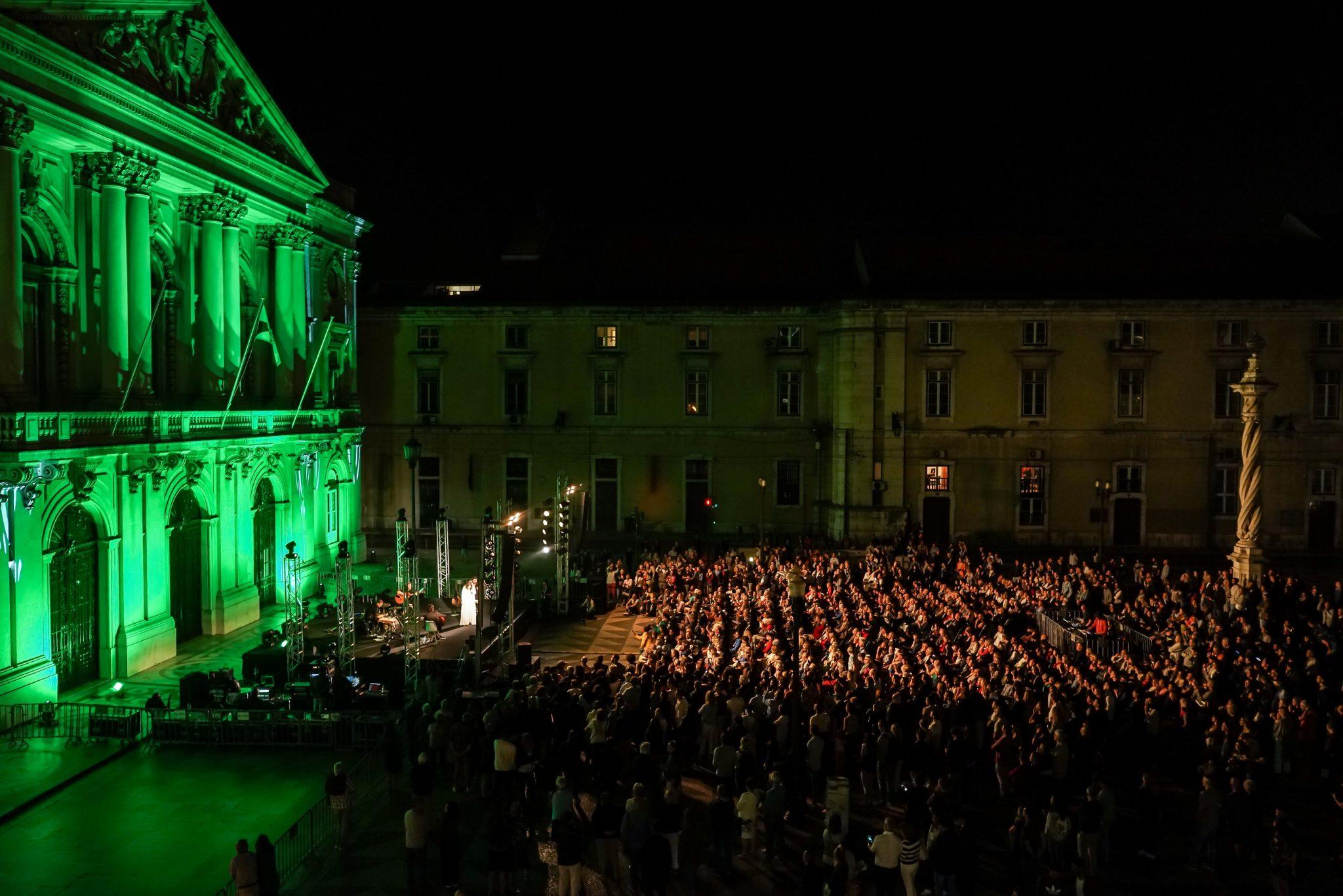 Plano lateral da Praça do Município, com os Paços do Concelho iluminados a verde. Dezenas de pessoas assistem ao concerto de Sara Correia
