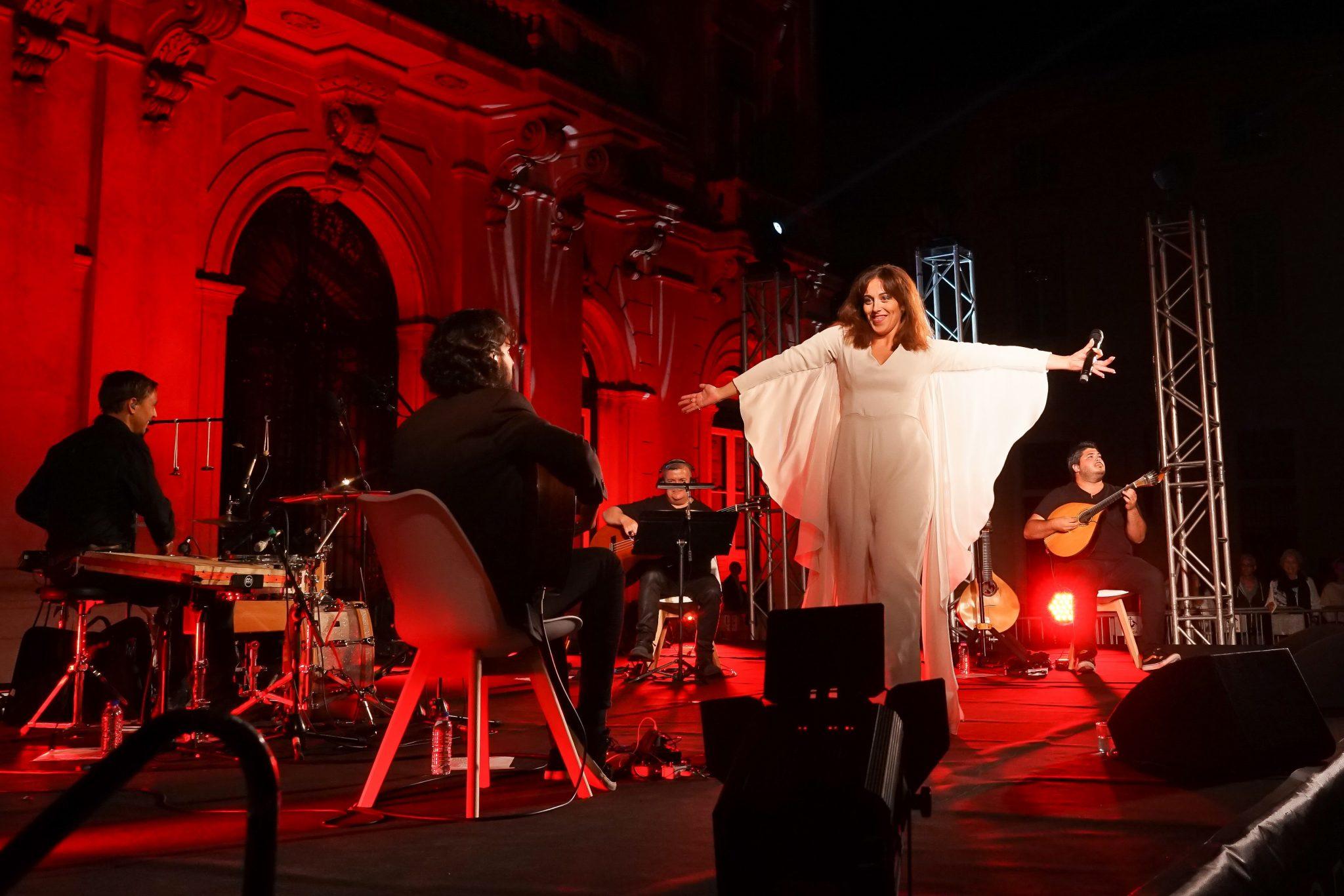 Fadista Sara Correia de braços abertos, virada para um dos quatro músicos que estiveram com ela em palco