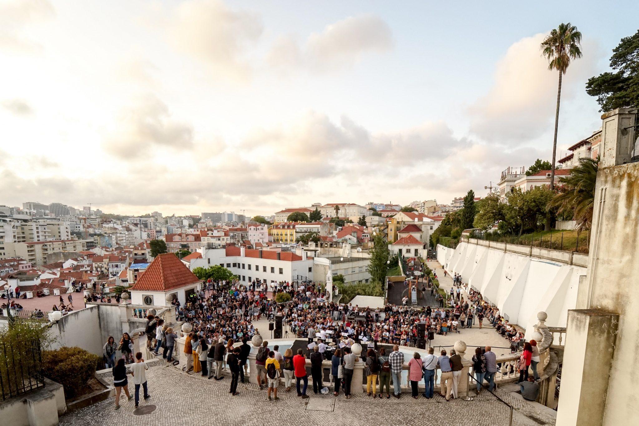 Pessoas de pé, de costas para o observador, num plano superior ao palco e a um outro grupo de pessoas, sentadas e de pé, de frente para o observador