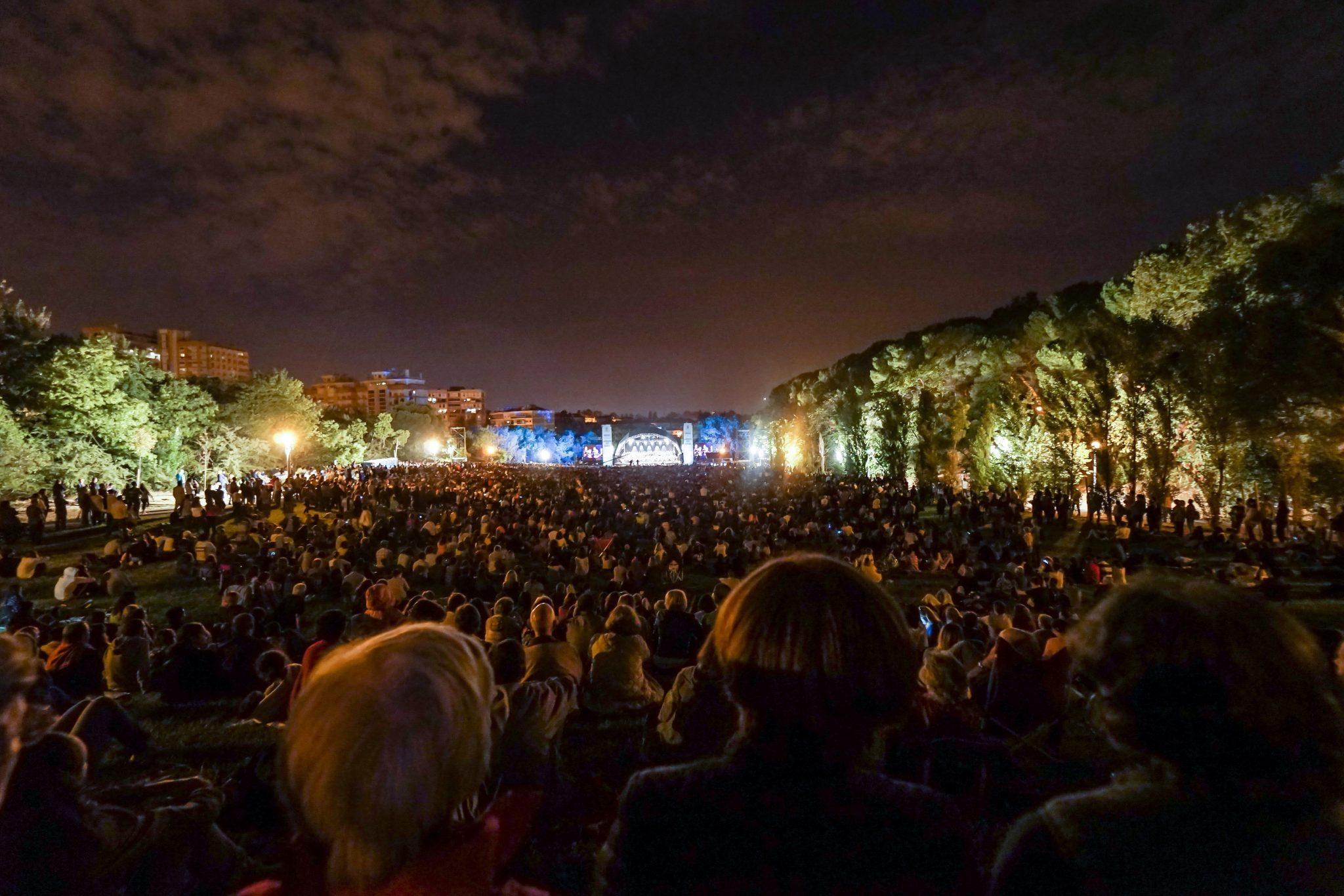 Num primeiro plano, de costas para o observador, centenas de pessoas sentadas num terreno relvado, viradas para um palco ao fundo, iluminado em tons de branco e azul.
