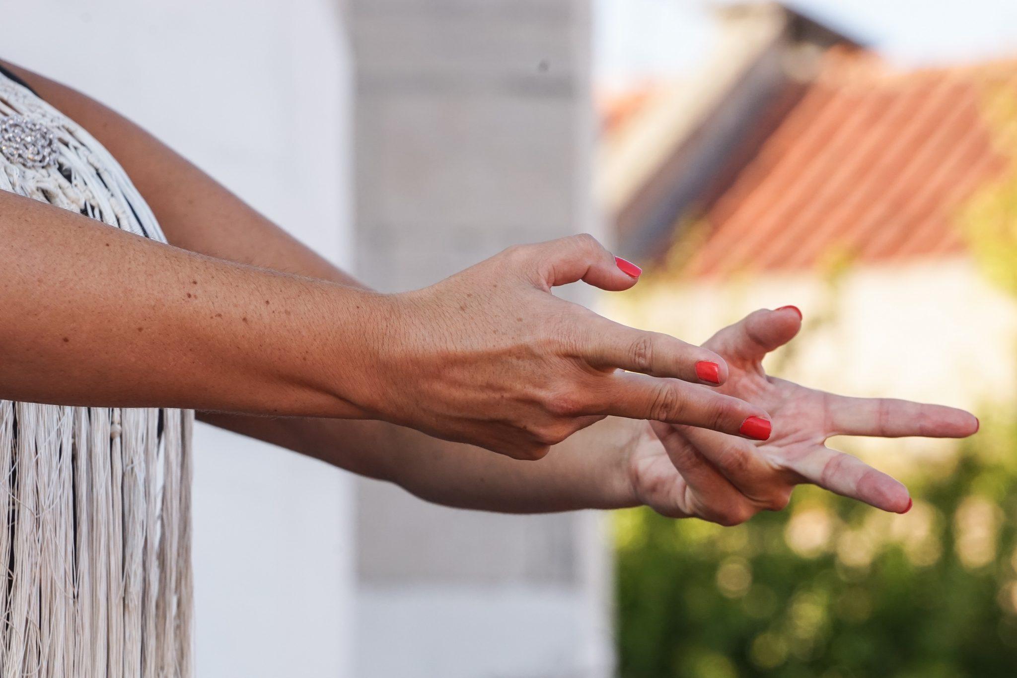 Pormenor das mãos de uma mulher, com alguns dedos enrolados, demonstrando um movimento do flamenco