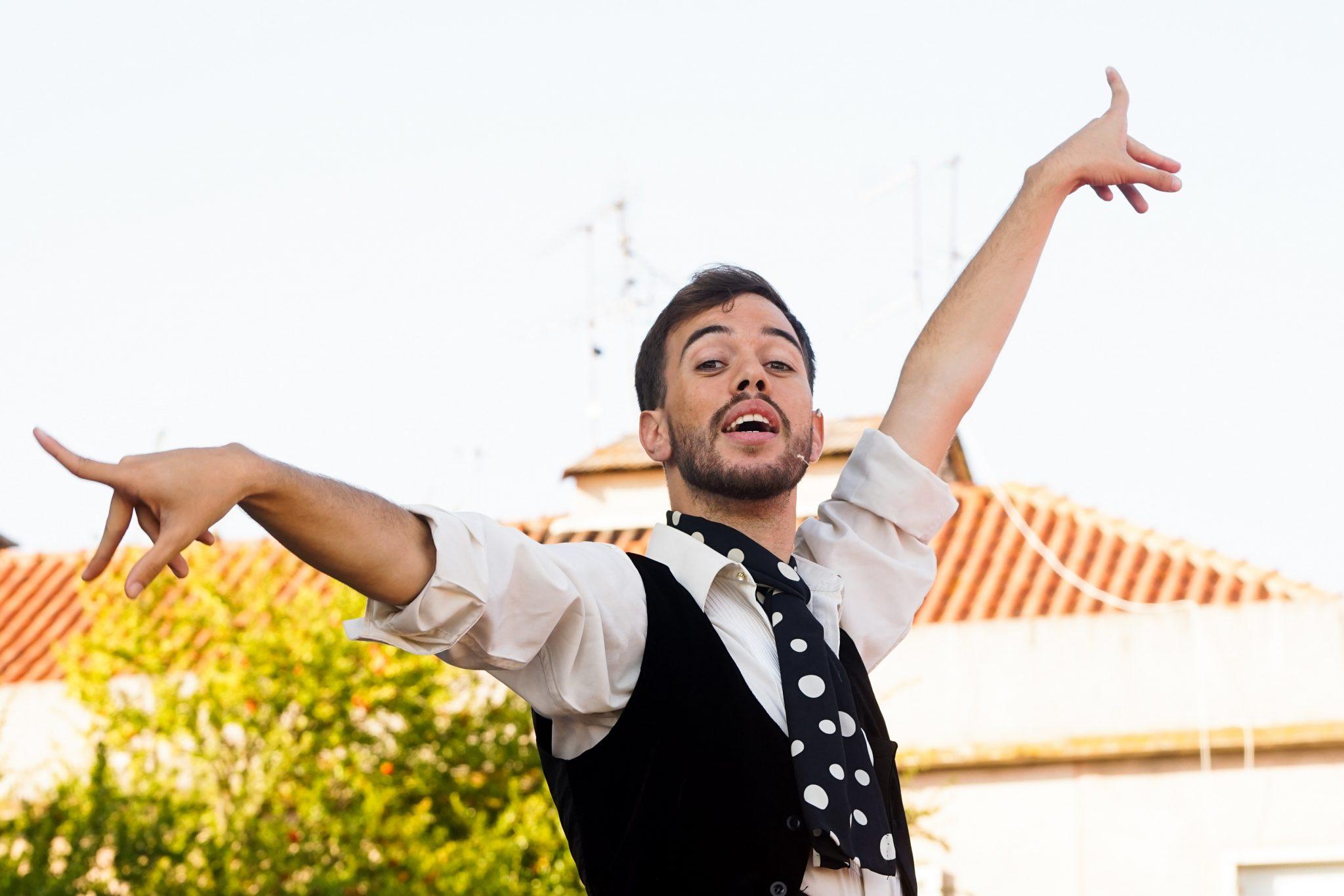 Um homem, de frente para o observador, dança com braço esticado para cima e outro esticado para o lado