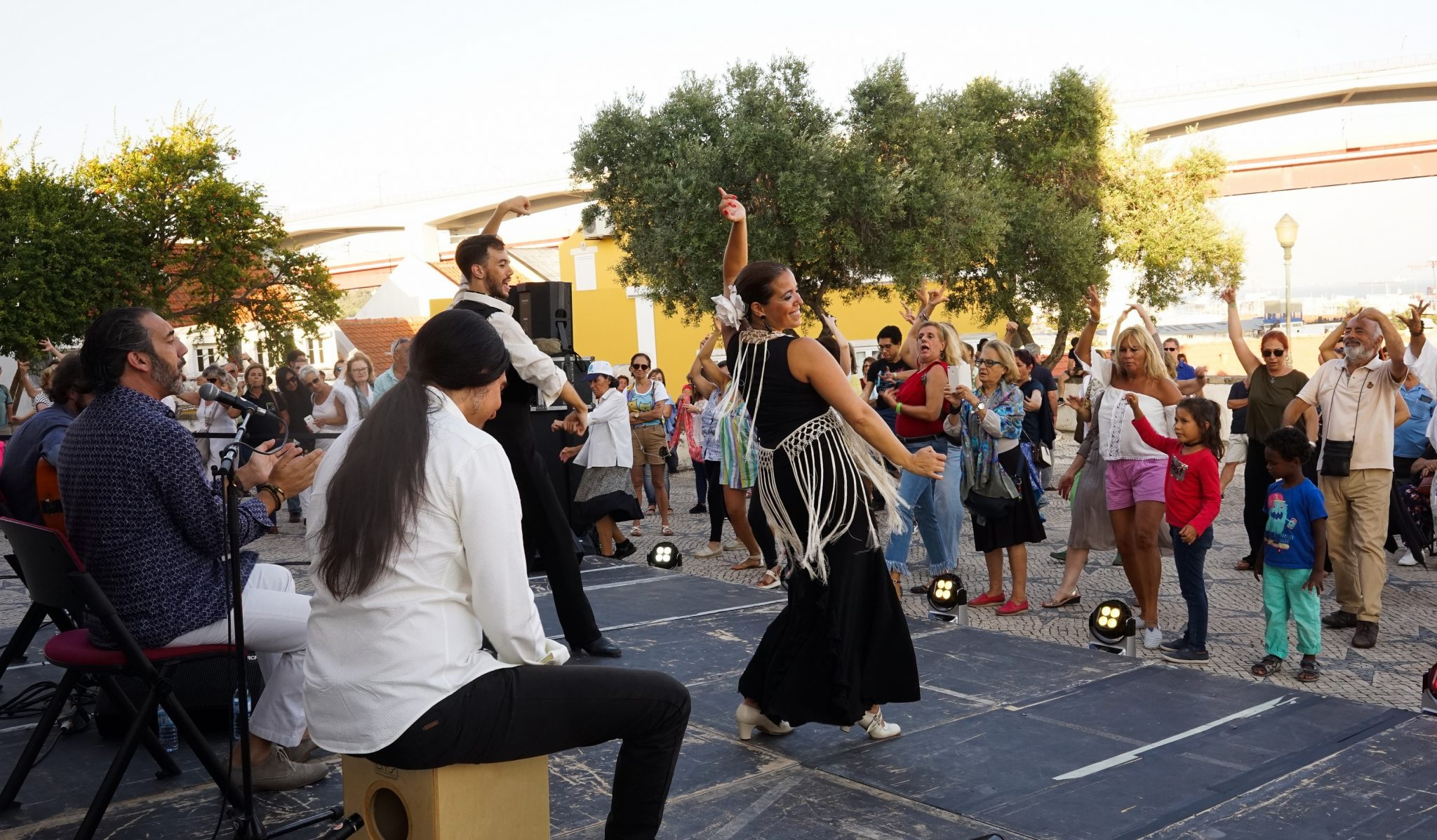 Dois bailarinos dançam flamenco ao som da música tocada por três músicos. À sua frente, um grupo de pessoas vai dançando