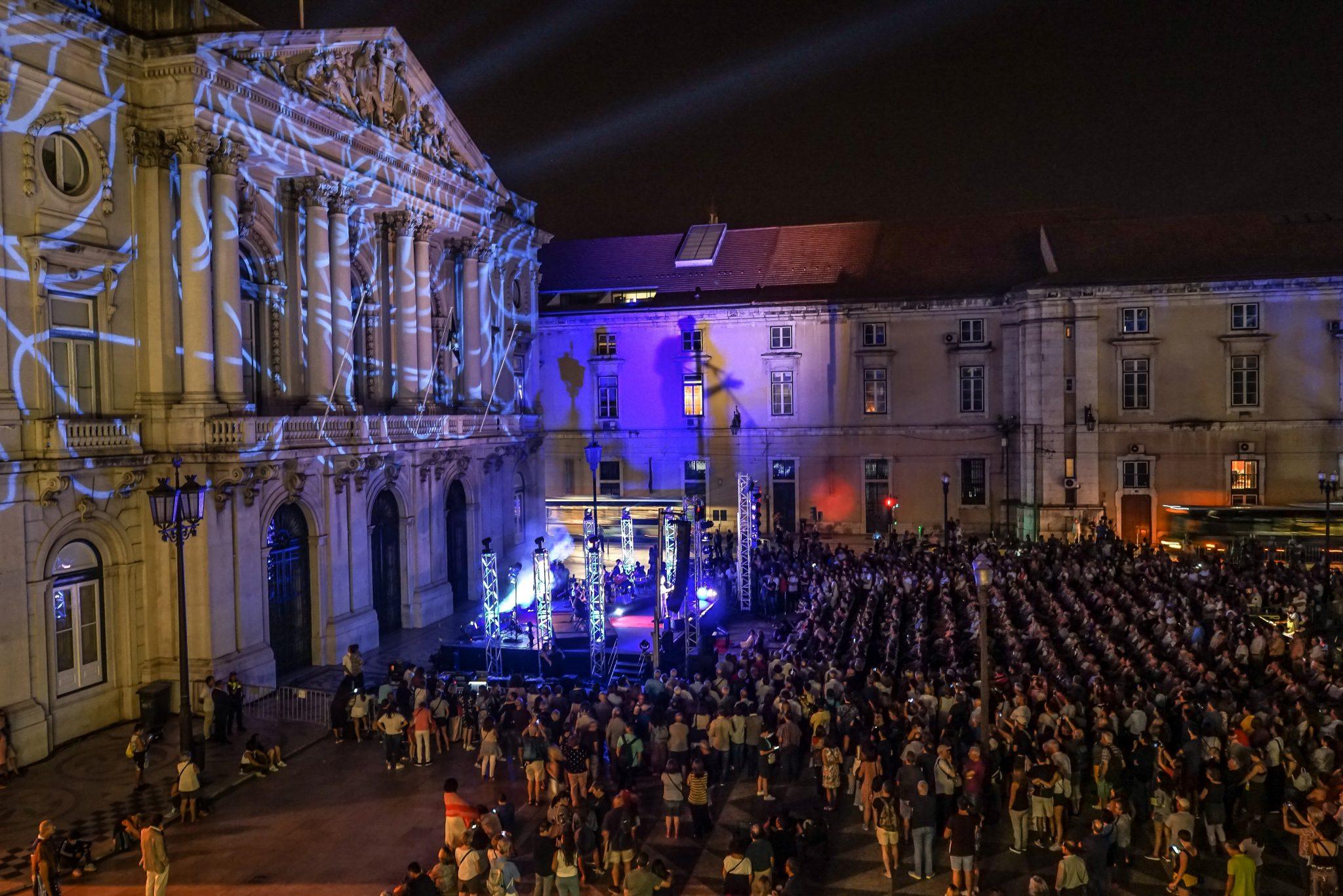 Praça do Município, de lado para o observador, à noite durante concerto, com pessoas sentadas e de pé