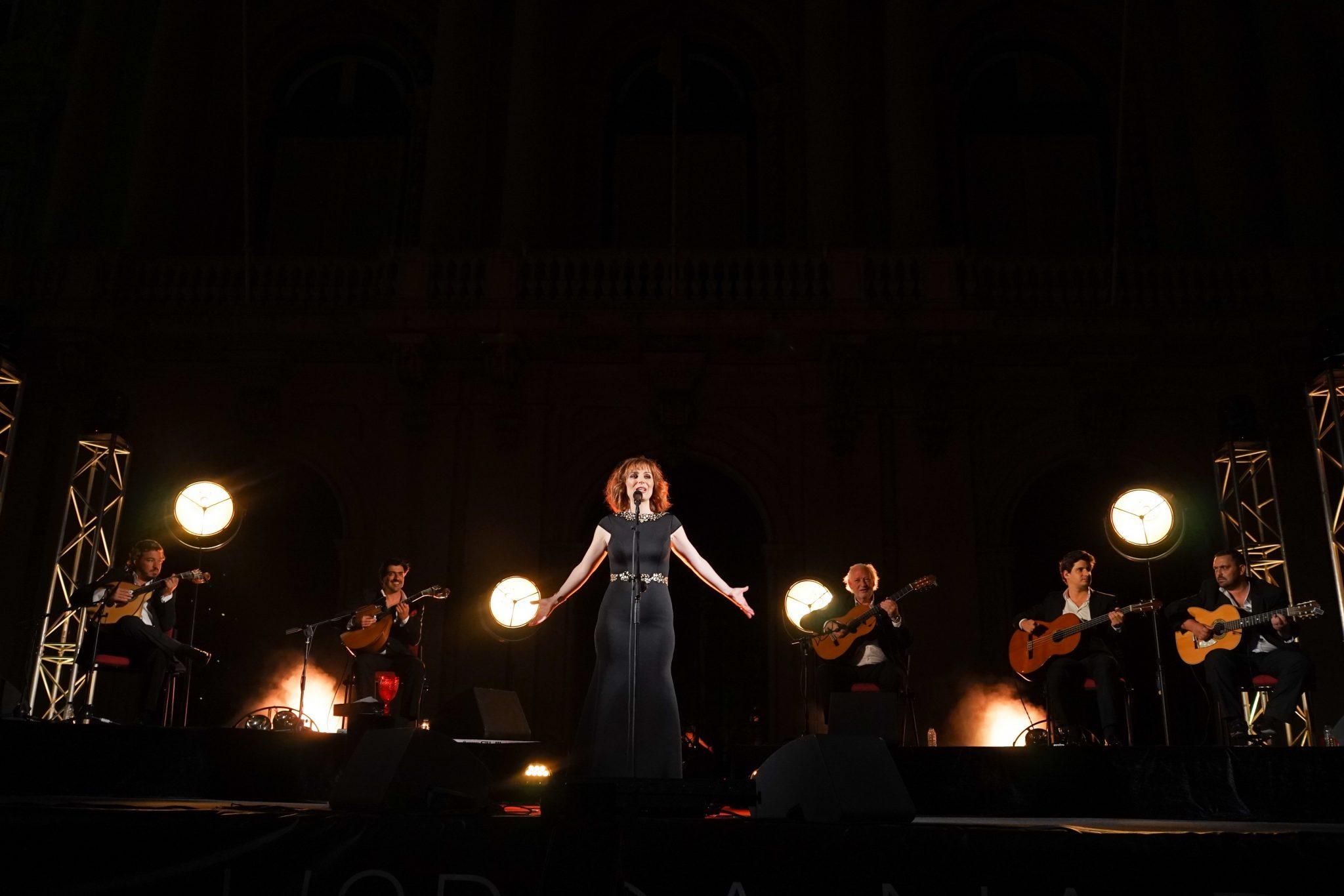 Cinco músicos a toca guitarra portuguesa e viola, sentados, acompanhados pela fadista Katia Guerreiro ao centro da imagem de braços abertos.