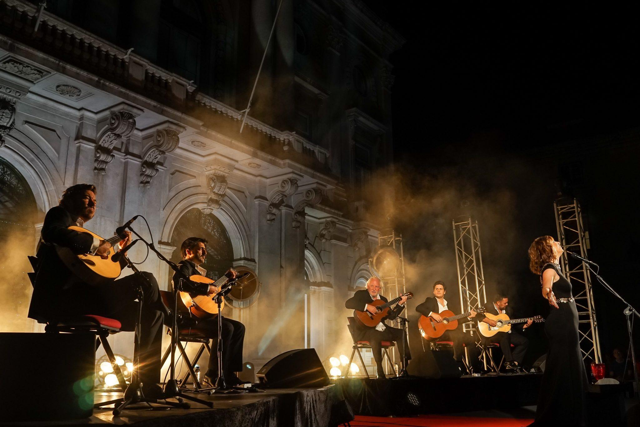 Músicos em palco, de lado para o observador, acompanham a fadista Katia Guerreiro