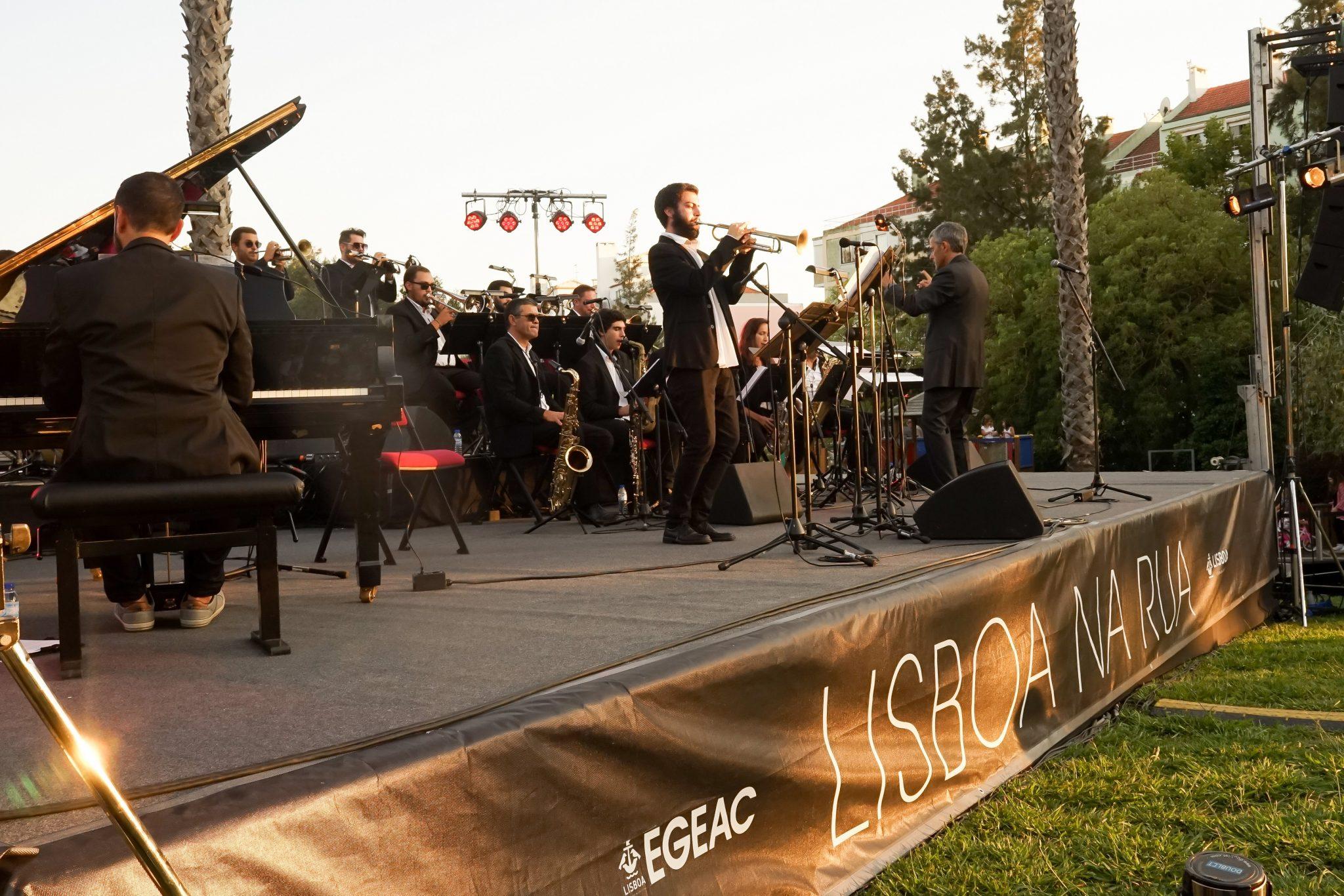 Músicos em palco, de lado para o observador, tocam trompete, piano e saxofone.