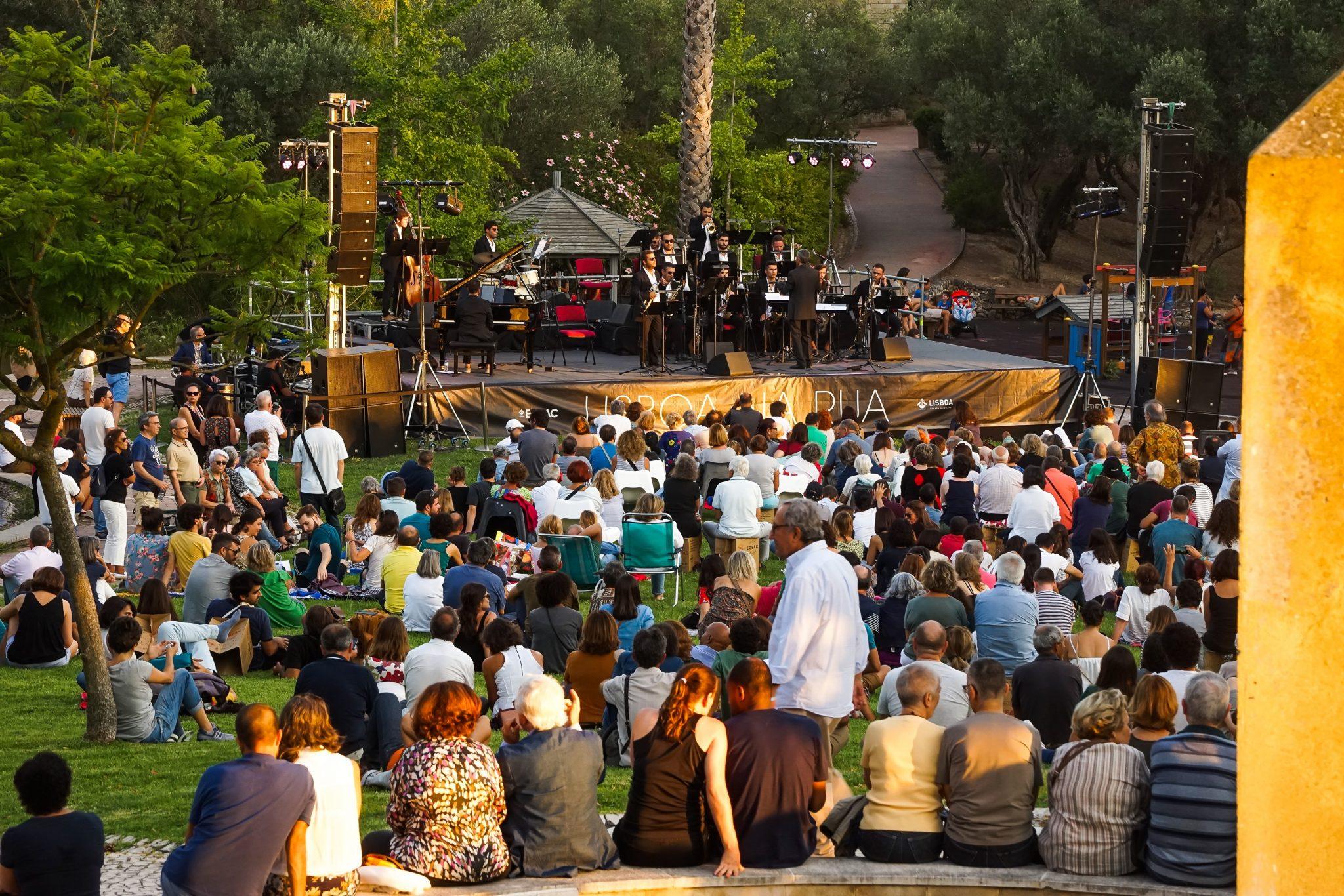 Pessoas sentadas no chão e em cadeiras, de costas para o observador, assistem a espectáculo de músicos em palco, de frente para o observador.