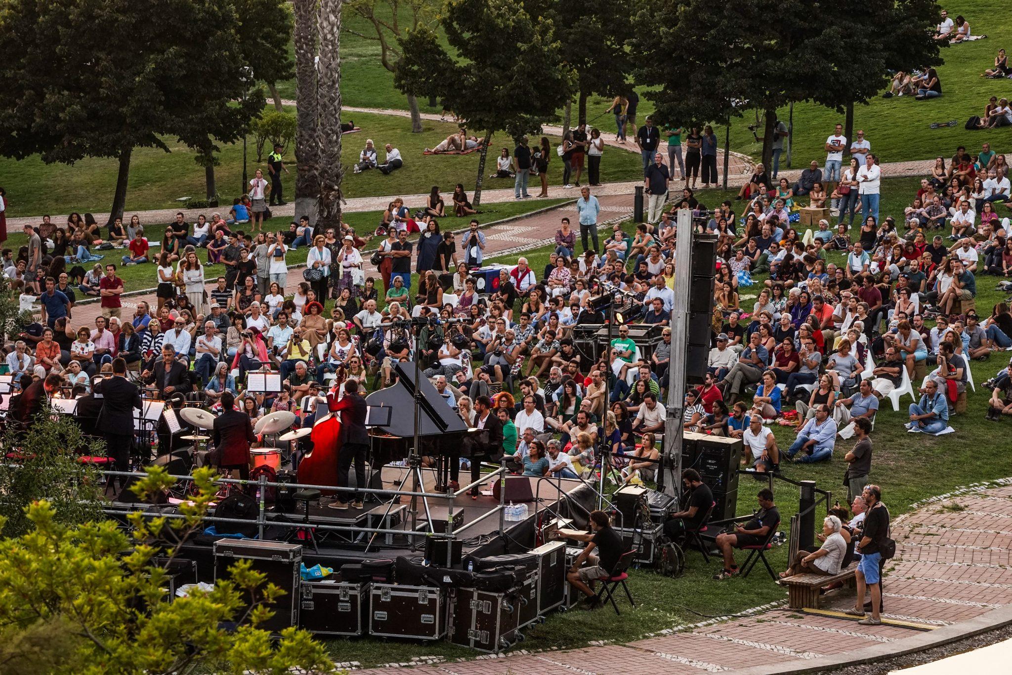 Pessoas sentadas num terreno relvado inclinado, de frente para o observador, olham para os músicos em palco, de costas para o observador