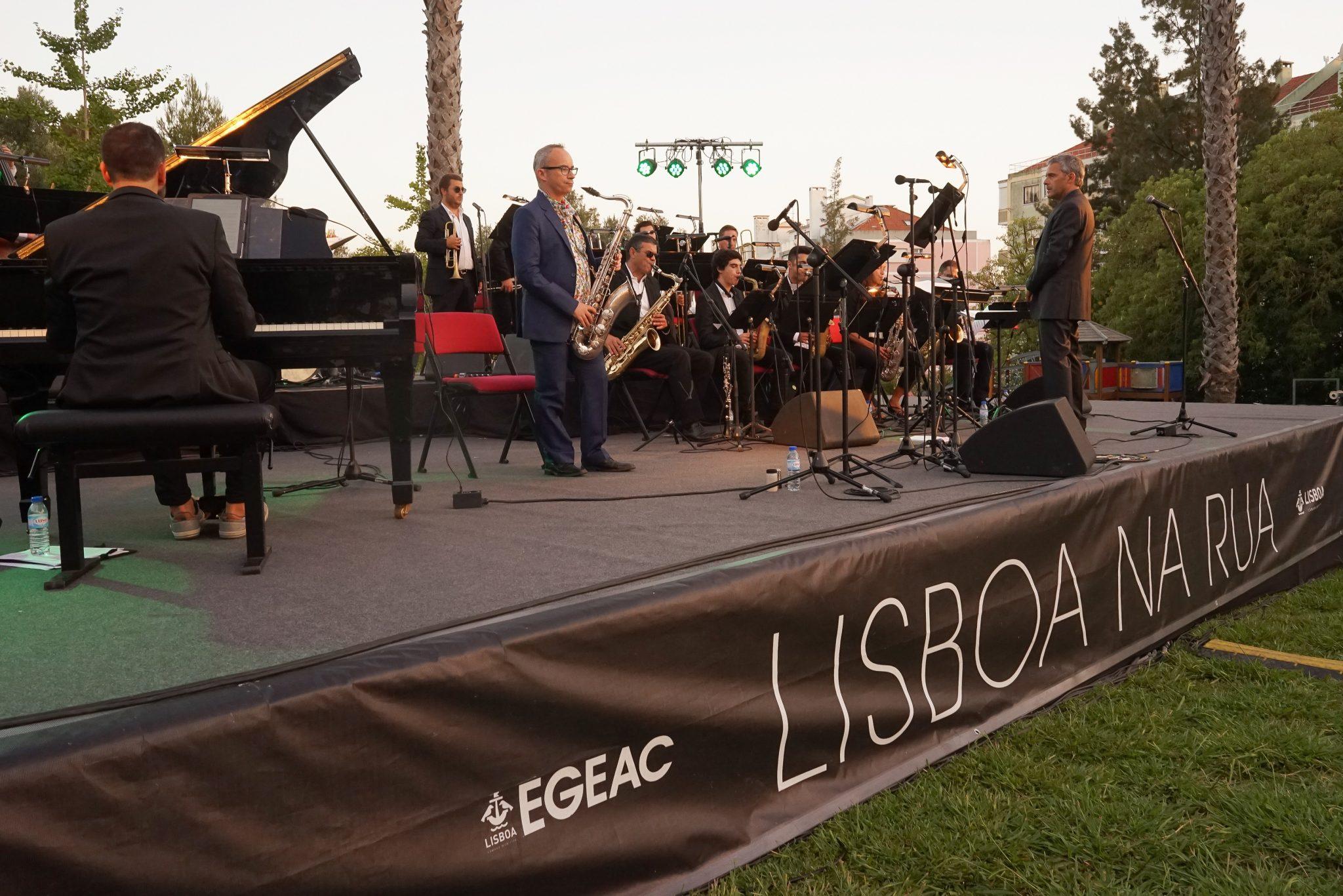 Músicos em palco, de lado para o observador, tocam piano e saxofone