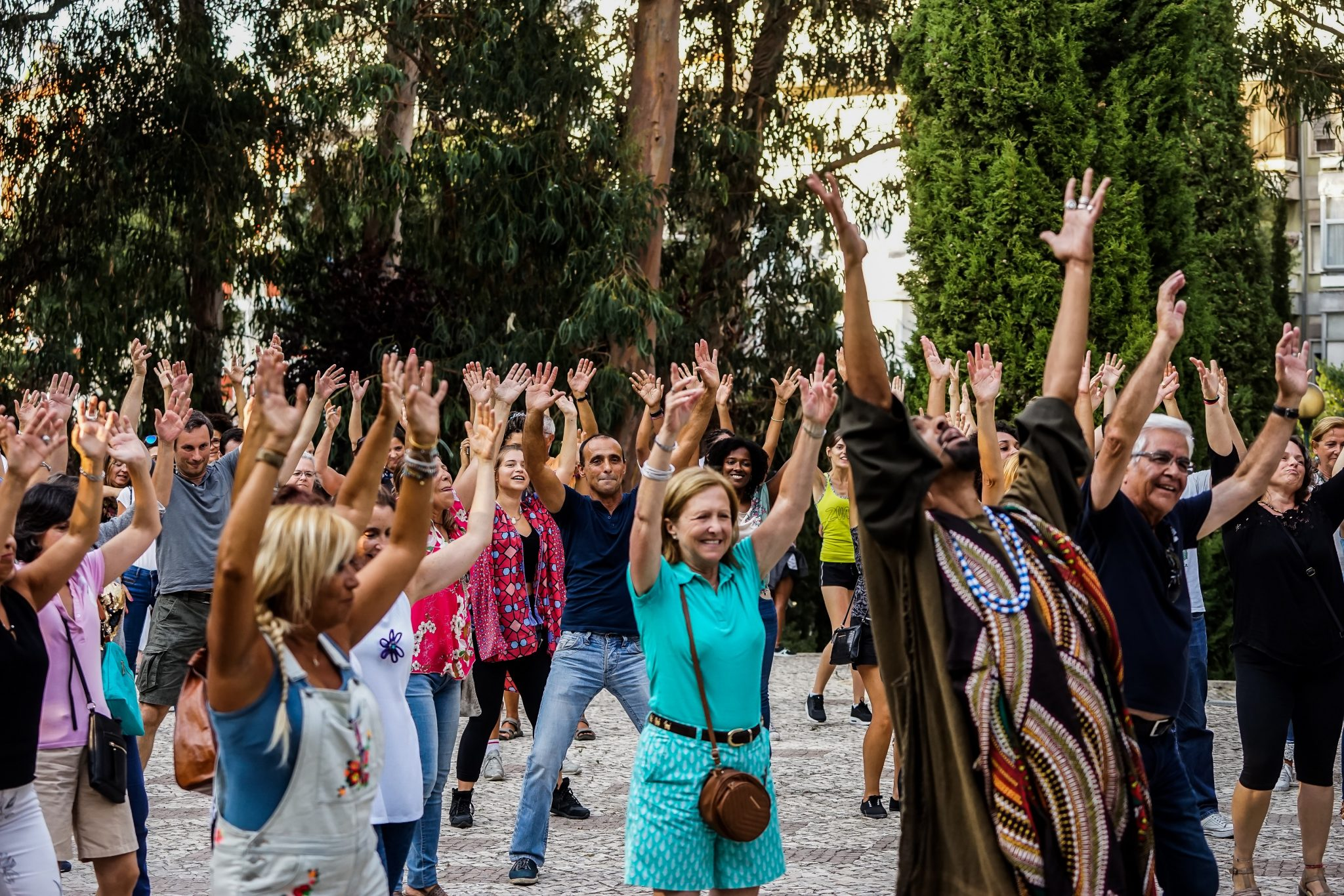Pessoas de pé, de frente para o observador, com os braços esticados para cima
