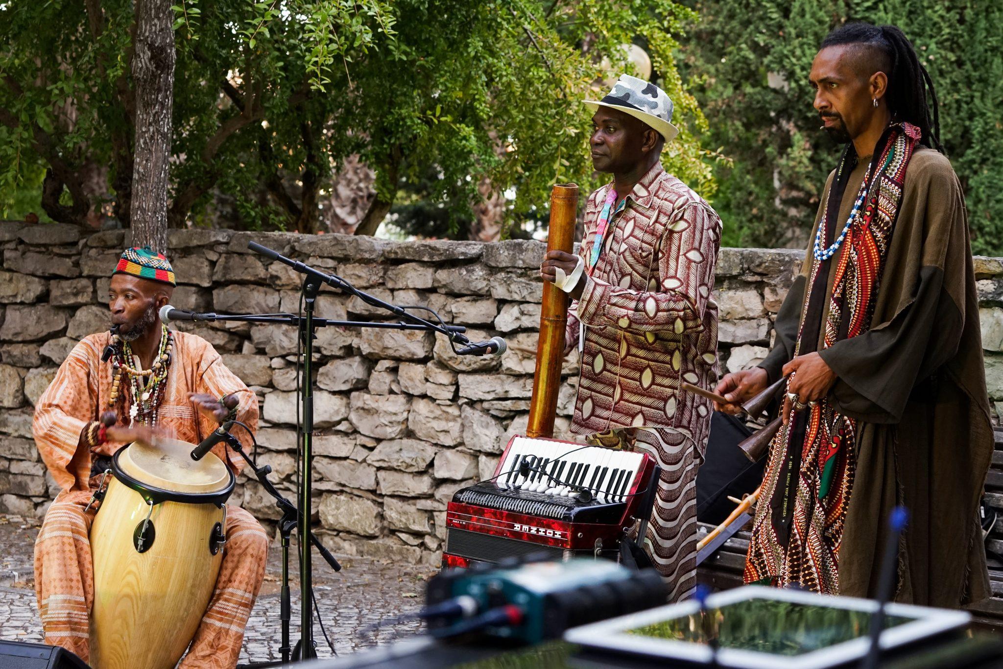 Três homens num palco com acordeão, pau de chuva e percussões