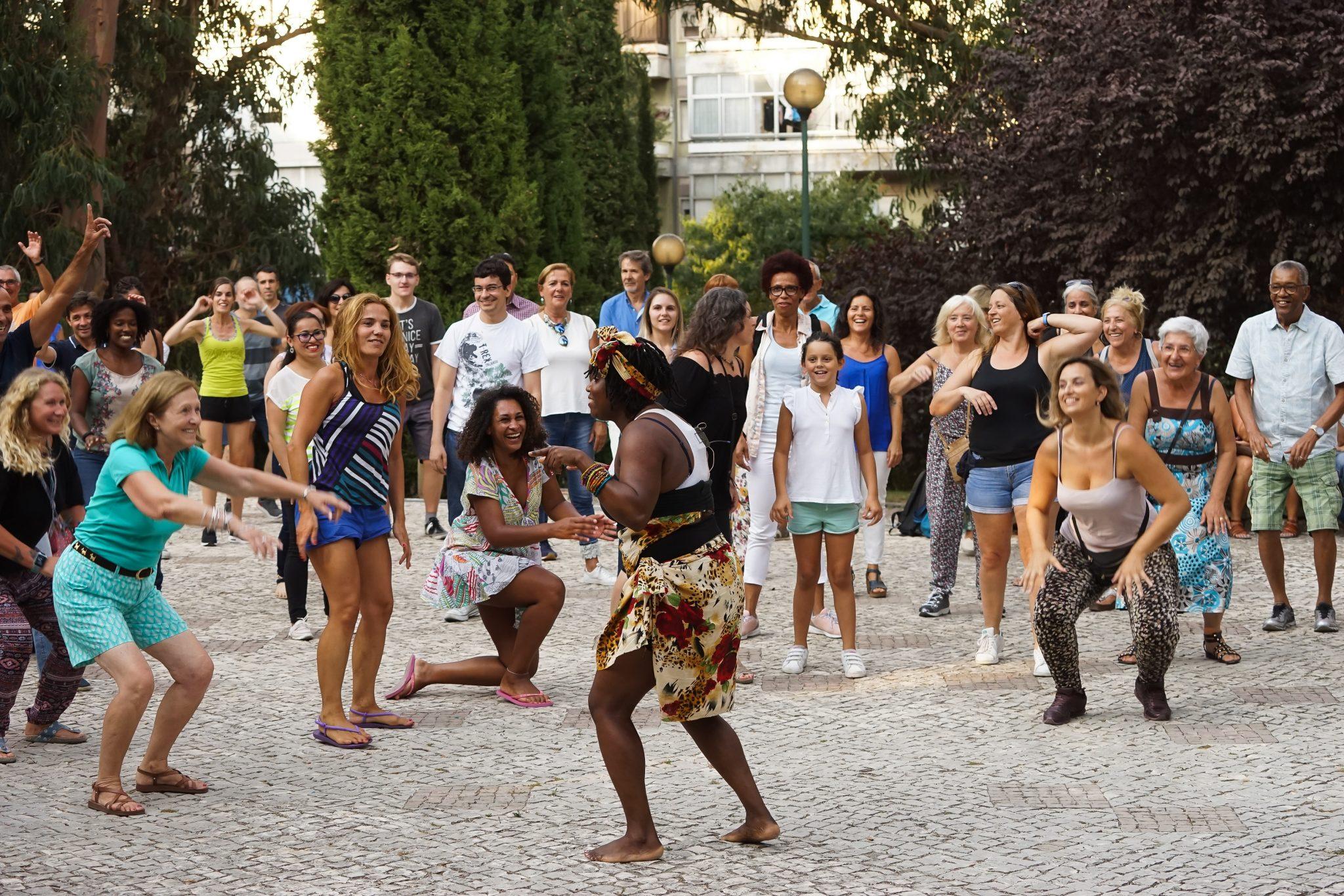 Grupo de pessoas de frente para o observador dança, seguindo os passos de uma mulher, de costas para o observador