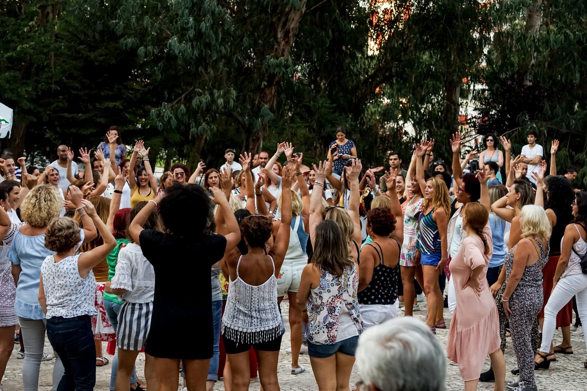 Grupo de pessoas em círculo, com os braços esticados para cima