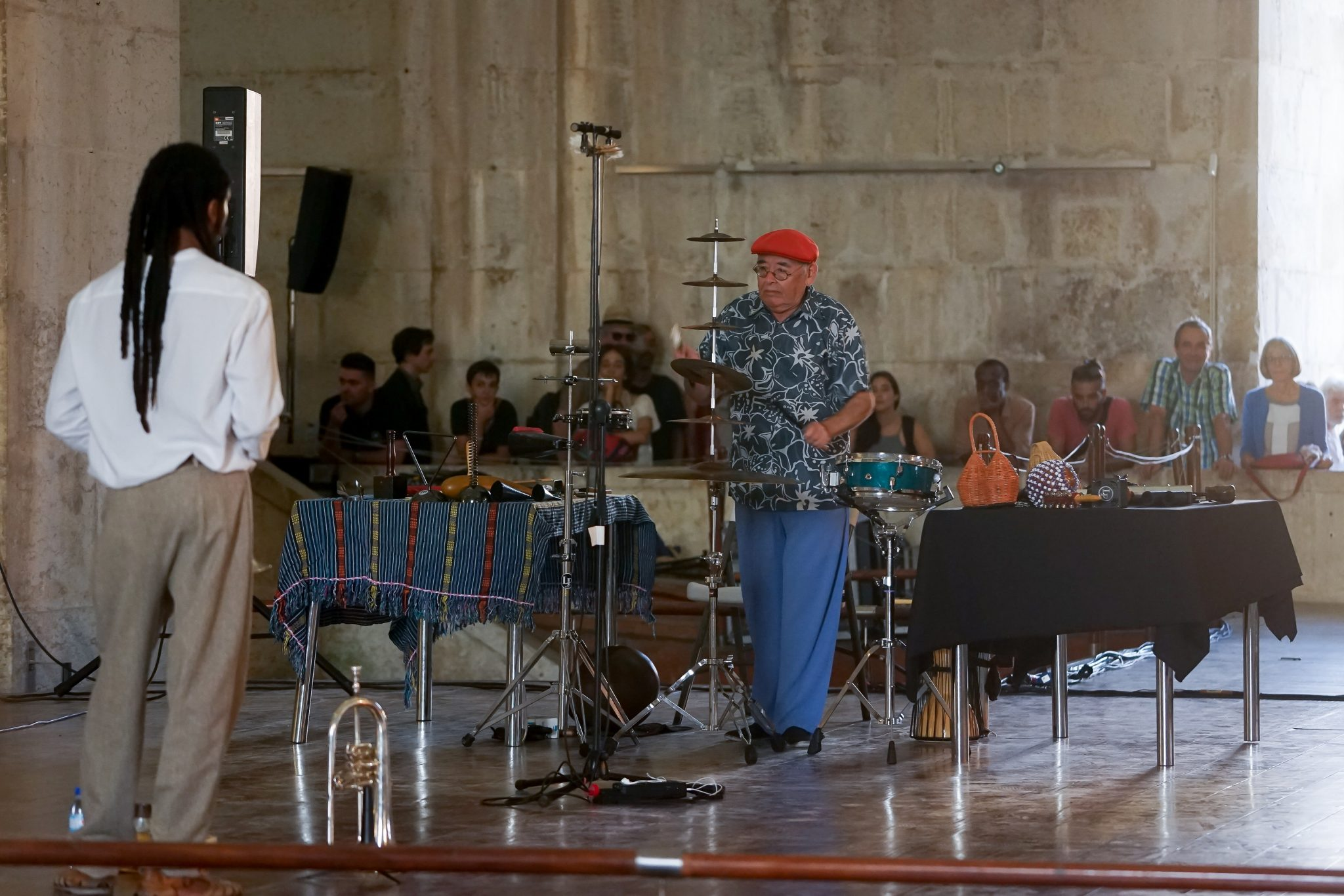 Os músicos Yaw Tembe, de costas para o observador, e Francisco Trindade, de frente para o observador, com uma boina vermelha, durante atuação num palco em cima da água. Ao fundo, um grupo de pessoas assiste ao concerto